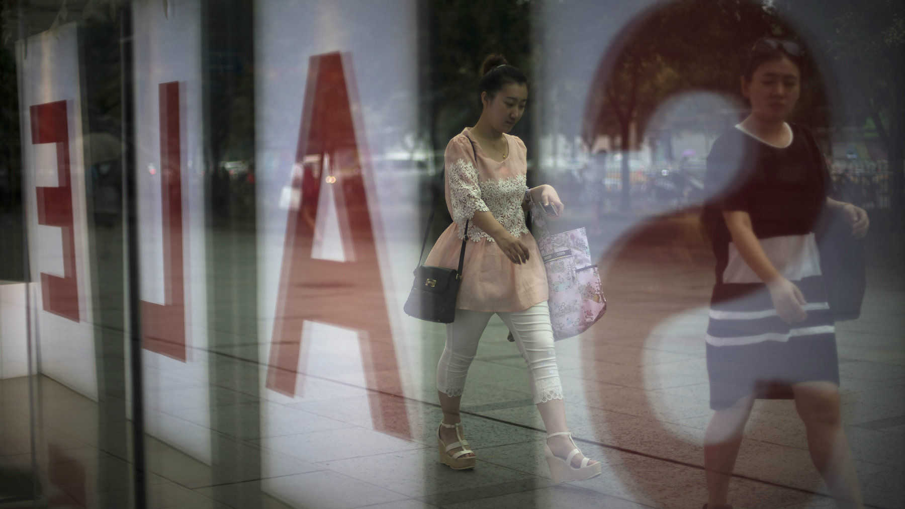 Women walk past a fashion outlet offering a sale at a shopping mall in Beijing.