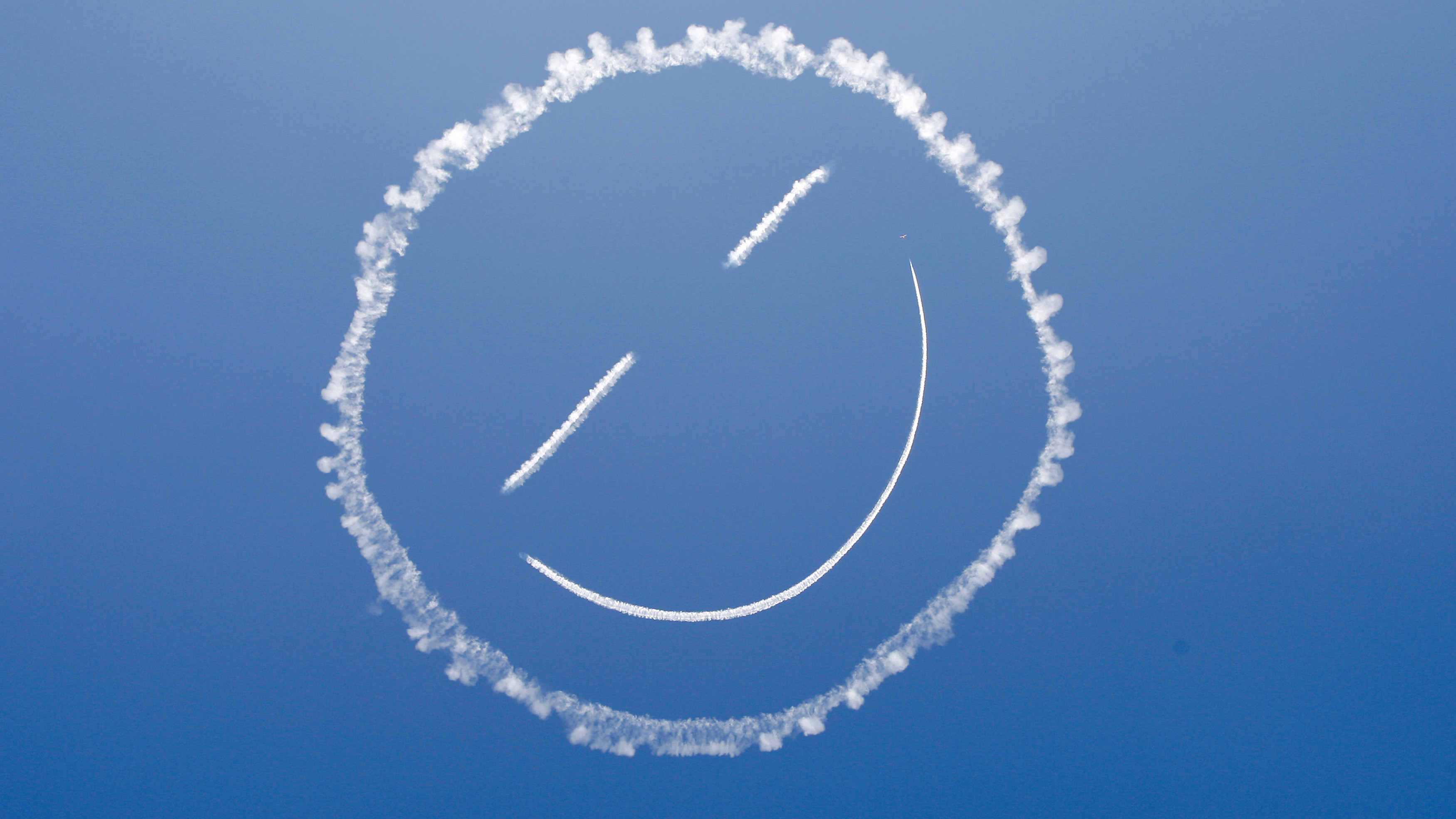 A sky writer draws a smiley face in the sky at start of Los Angeles County Air Show at the General William J. Fox Airfield in Lancaster