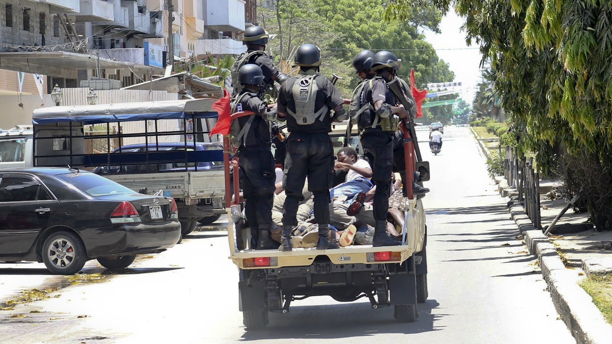 In this photo taken Monday, Oct. 26th, 2015 and made available Wednesday, Oct. 28th, 2015, police special forces ride in the back of a vehicle with unidentified men they had arrested, in the Darajani area of Stone Town, Zanzibar, a semi-autonomous island archipelago of Tanzania. Zanzibar's election commission chief announced Wednesday that the results of the island archipelago's presidential election have been nullified because of alleged irregularities, saying that the decision was taken because of several issues with the voting process, but did not say when another election would take place.