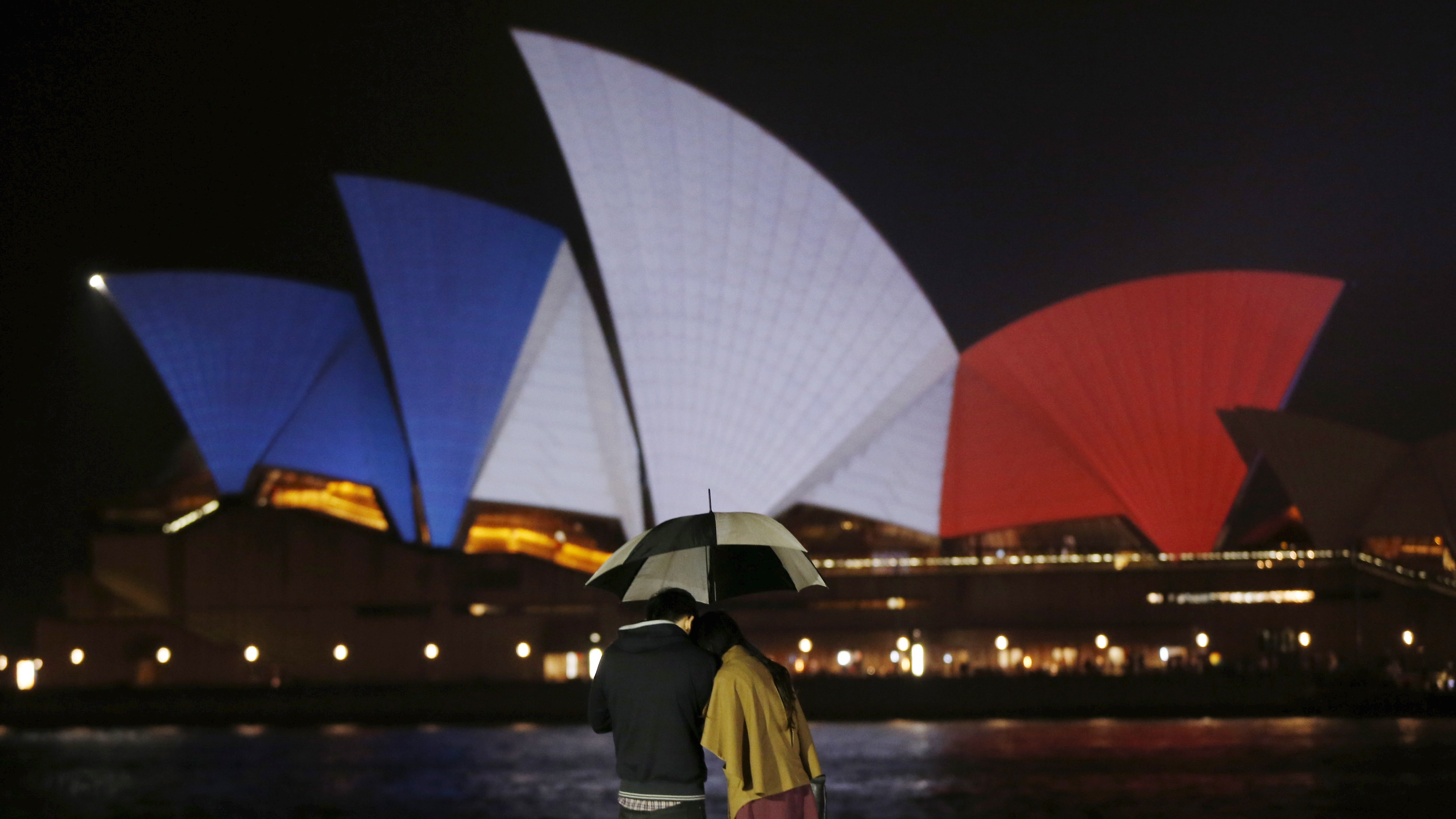 A couple stands in the rain as the blue, white and red colors of France's national flag are projected onto the sails of Sydney's Opera House in Australia on Nov. 14.