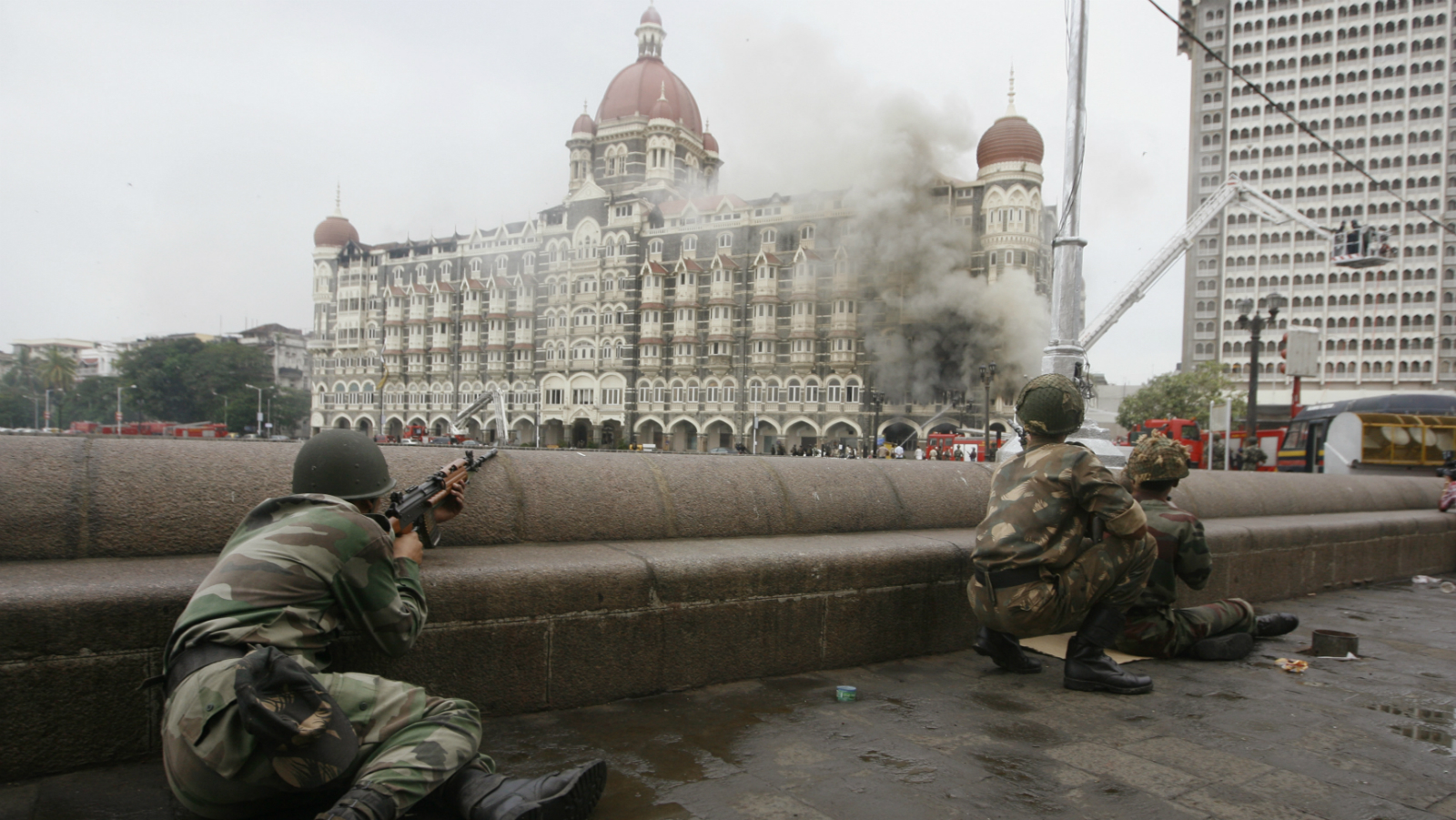 Indian army soldiers take position during a gun battle at the Taj Mahal hotel (seen in the background) in Mumbai November 29, 2008. Operations by Indian commandos to dislodge Islamist militants at Mumbai's Taj Mahal hotel ended on Saturday, Indian television channels quoted officials as saying. The hotel came under heavy gunfire and flames leaped out of the building shortly before the announcement. REUTERS/Desmond Boylan (INDIA)