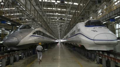 A worker walks between two bullet trains at a high speed railway maintenance station in China's, Shaanxi province.