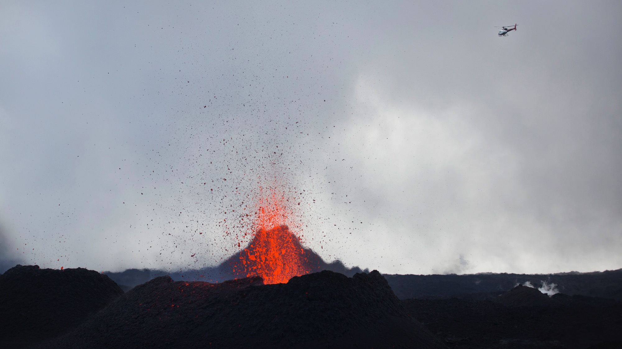 """A helicopter flies over as lava erupts from the Piton de la Fournaise """"Peak of the Furnace"""" volcano, on the southeastern corner of the Indian Ocean island of Reunion Saturday, Aug. 1, 2015. Spewing red-hot lava, one of the most active volcanoes in the world is currently erupting on this Indian Ocean island, where the world's attention has been focused since a wing fragment believed to be from the missing Malaysian jet was discovered washed up on a beach. (AP Photo/Ben Curtis)"""