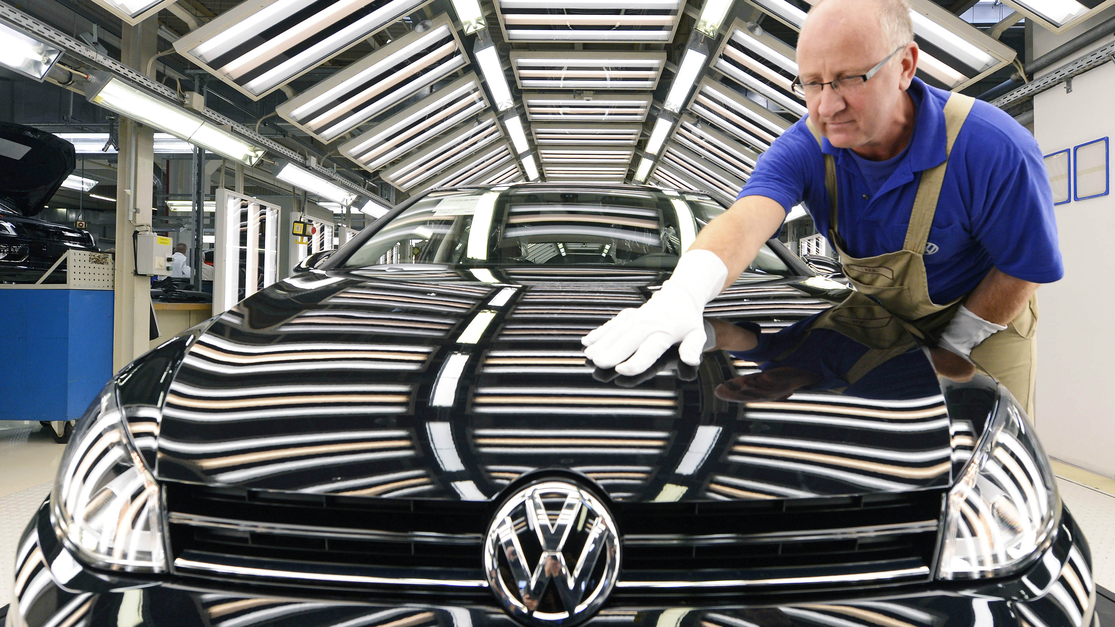 "FILE - In this Nov. 9, 2012 file photo worker Michael Keil checks a Golf VII car during a press tour at the plant of the German car manufacturer Volkswagen AG (VW) in Zwickau, central Germany. German automaker Volkswagen AG said Wednesday, July 31, 2013 net profit fell 50 percent in the second quarter in ""a difficult market environment"" but said it will still achieve its earnings goal for the year. Net profit fell to 2.85 billion euros from 5.70 billion in the same quarter a year ago. Revenue rose 8.5 percent to 52.1 billion euros. (AP Photo/Jens Meyer,File)"
