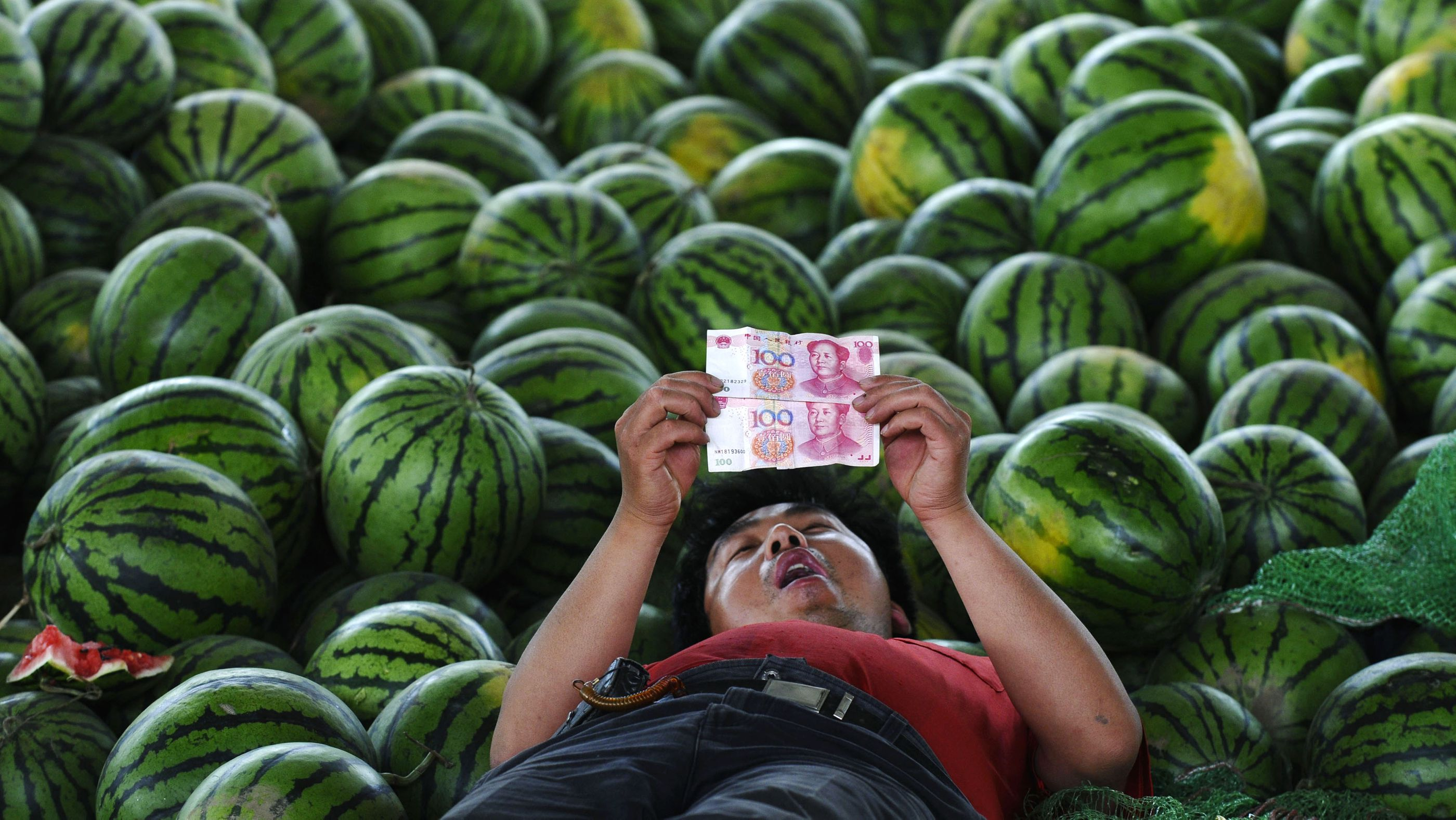 The right way to pronounce yuanand its not like in all those a watermelon vendor looks at yuan banknotes at a market in changzhi shanxi province june biocorpaavc Images