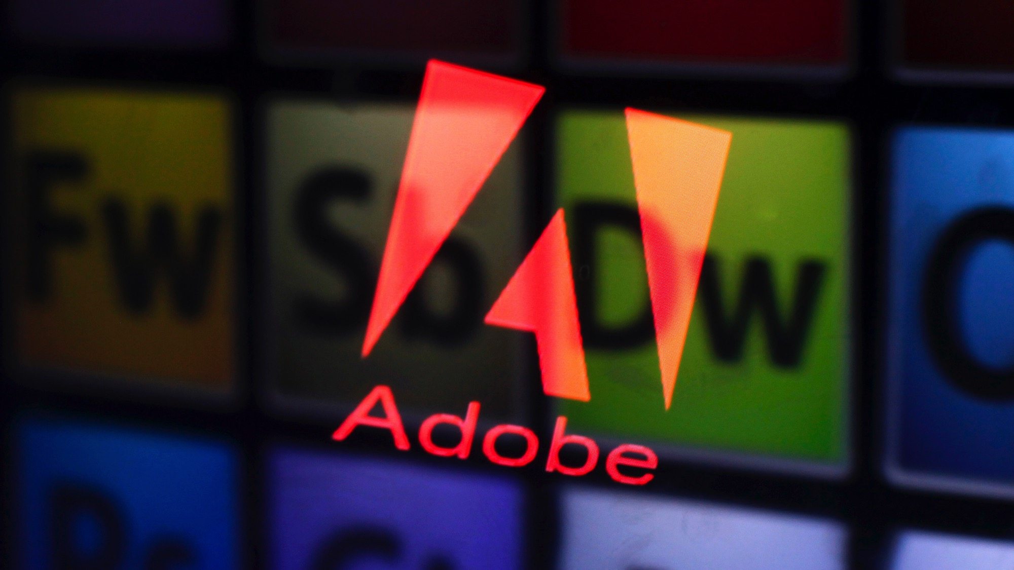 An Adobe logo and Adobe products are seen reflected on a monitor display and an iPad screen, in this picture illustration taken in the central Bosnian town of Zenica July 8, 2013. Picture taken July 8, 2013.