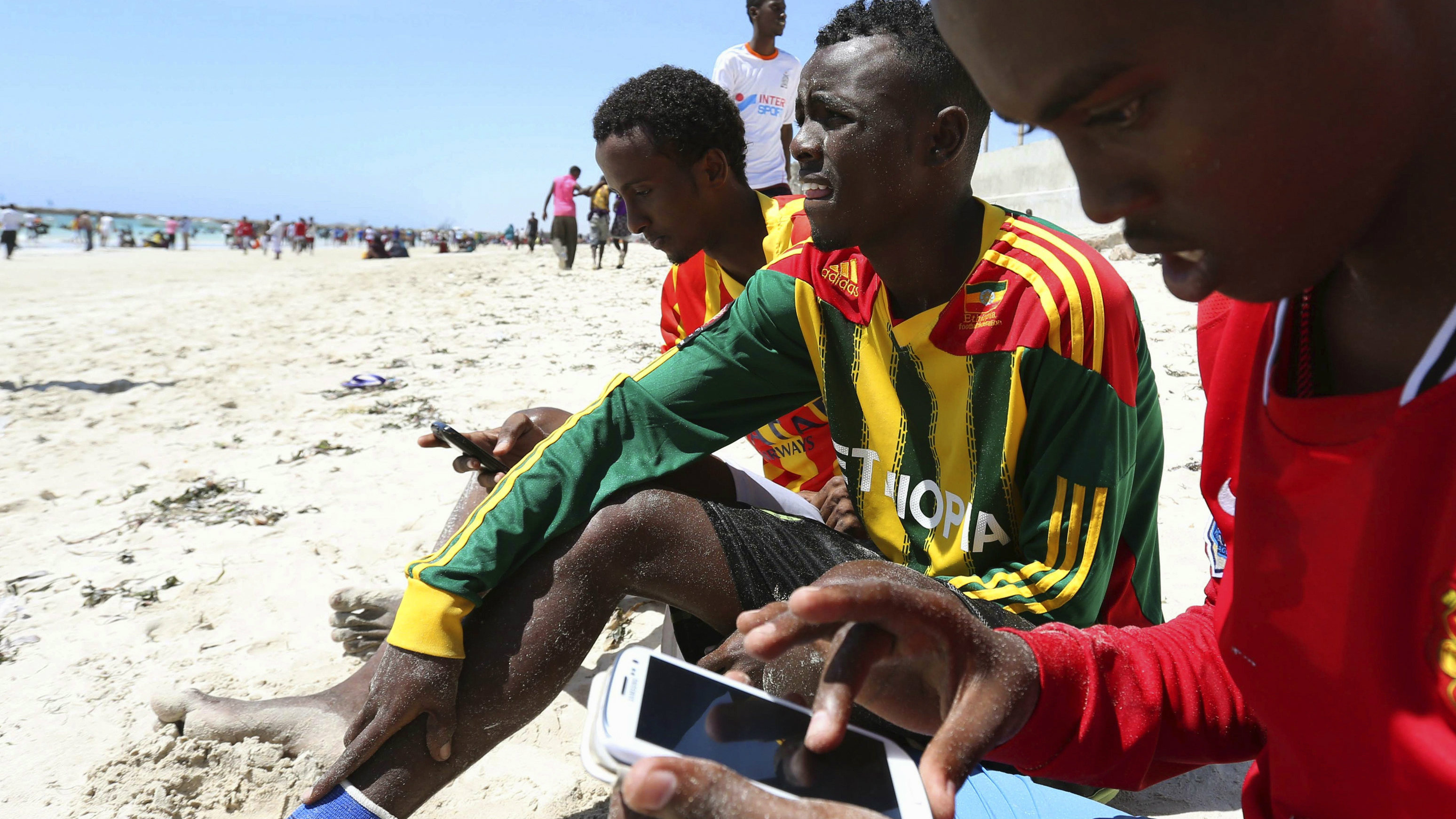"""A Somali man browses the internet on his mobile phone at the beach along the Indian Ocean coastline in Somalia's capital Mogadishu, January 10, 2014. Somali rebel group al Shabaab has banned the use of the Internet in the Horn of Africa country, giving telecom operators 15 days to comply with the order, the militants said. """"Any company or person who fails to comply with the rule will be dealt with according to the Islamic sharia,"""" the group said in a statement posted on the Internet. REUTERS/Feisal Omar (SOMALIA - Tags: CIVIL UNREST POLITICS ENVIRONMENT SOCIETY SCIENCE TECHNOLOGY BUSINESS TELECOMS)"""