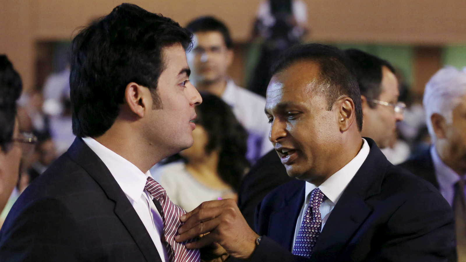 """Anil Ambani, chairman of the Reliance Anil Dhirubhai Ambani Group, adjusts the tie of his nephew Akash Ambani, son of Mukesh Ambani, chairman of Reliance Industries Limited, during the launch of """"Digital India Week"""" in New Delhi, India, July 1, 2015. India is reinvigorating an $18 billion campaign to provide fast internet connections for all, with a """"digital week"""" aimed at popularising Prime Minister Narendra Modi's campaign promise to connect 250,000 villages in India by 2019. REUTERS/Adnan Abidi"""
