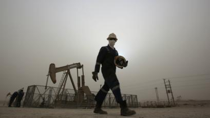 An oil worker walks by an oil pump during a sandstorm that blew in, in the desert oil fields of Sakhir, Bahrain.