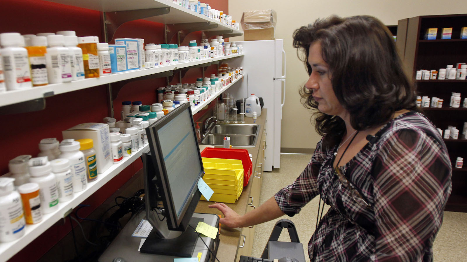 In this Jan. 24, 2012 photo, Terri Kroh, the director of pharmacy services at Duquesne University's Center for Pharmacy Services fills a prescription at the store in the Hill District of Pittsburgh. Duquesne has stepped in to fill a difficult role — delivering basic health care and medications in a poor inner city neighborhood. The school says the program is the first of its kind in the nation, and they hope it will be a model for other inner cities. ()
