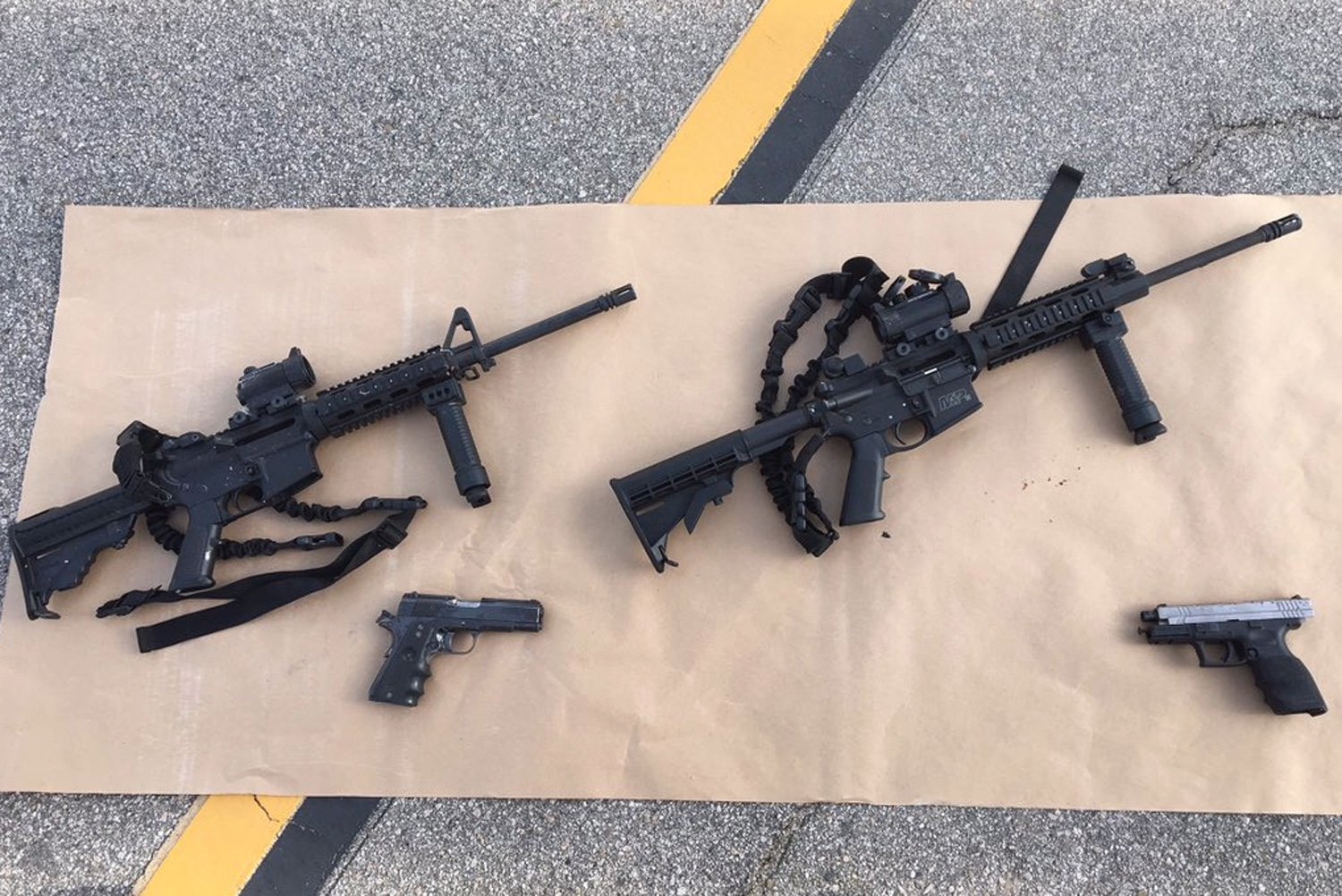 This photo provided by the San Bernardino County Sheriff's Department shows weapons carried by suspects at the scene of a shootout in San Bernardino, Calif. Multiple attackers opened fire on a banquet at a social services center for the disabled in San Bernardino on Wednesday, Dec. 2, 2015, killing multiple people and sending police on a manhunt for suspects. (San Bernardino County Sheriff's Department via AP)