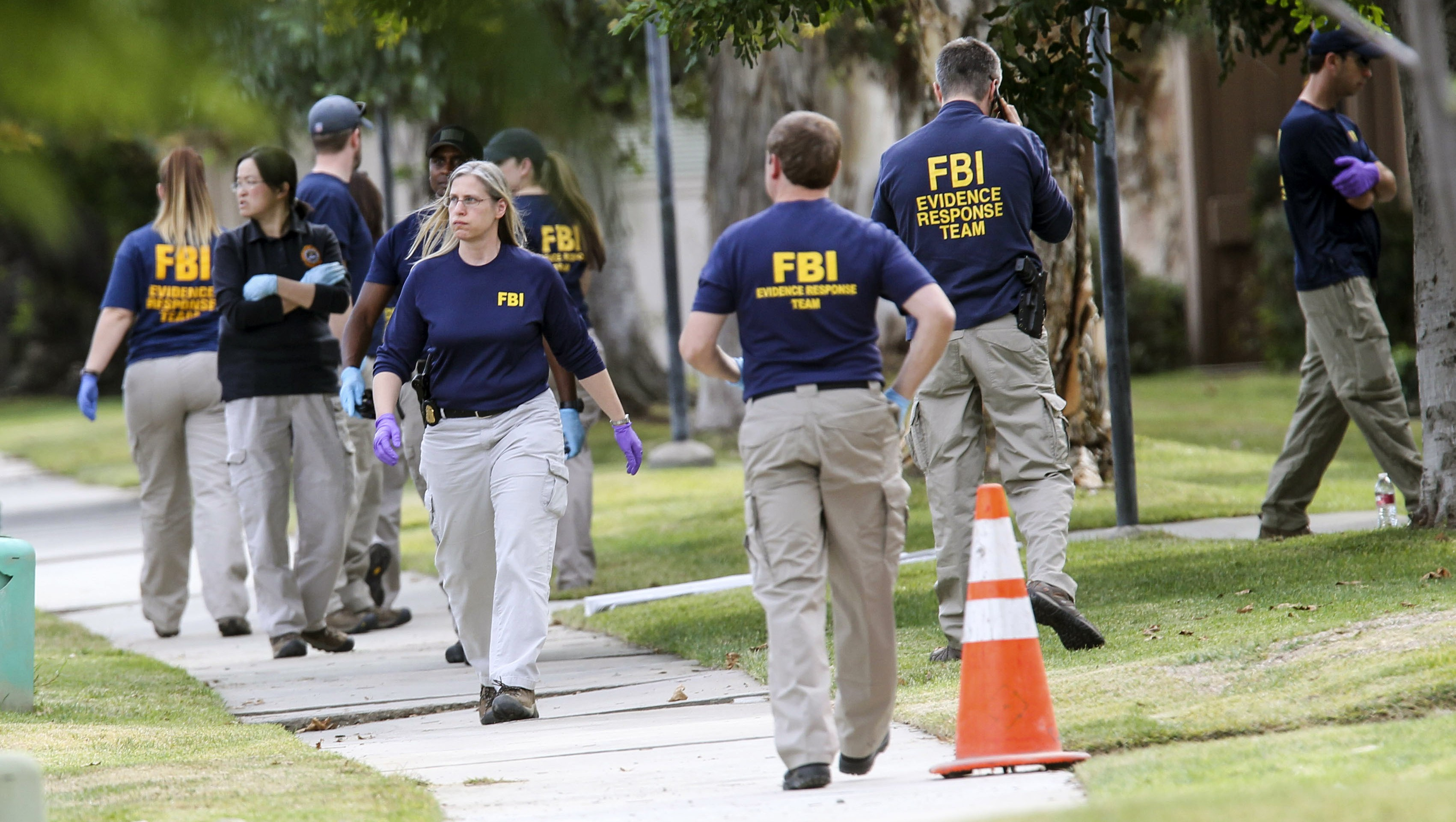 FBI agents search outside a home in connection to the shootings in San Bernardino, Thursday, Dec. 3, 2015, in Redlands, Calif. A heavily armed man and woman opened fire Wednesday on a holiday banquet for his co-workers, killing multiple people and seriously wounding others in a precision assault, authorities said. Hours later, they died in a shootout with police