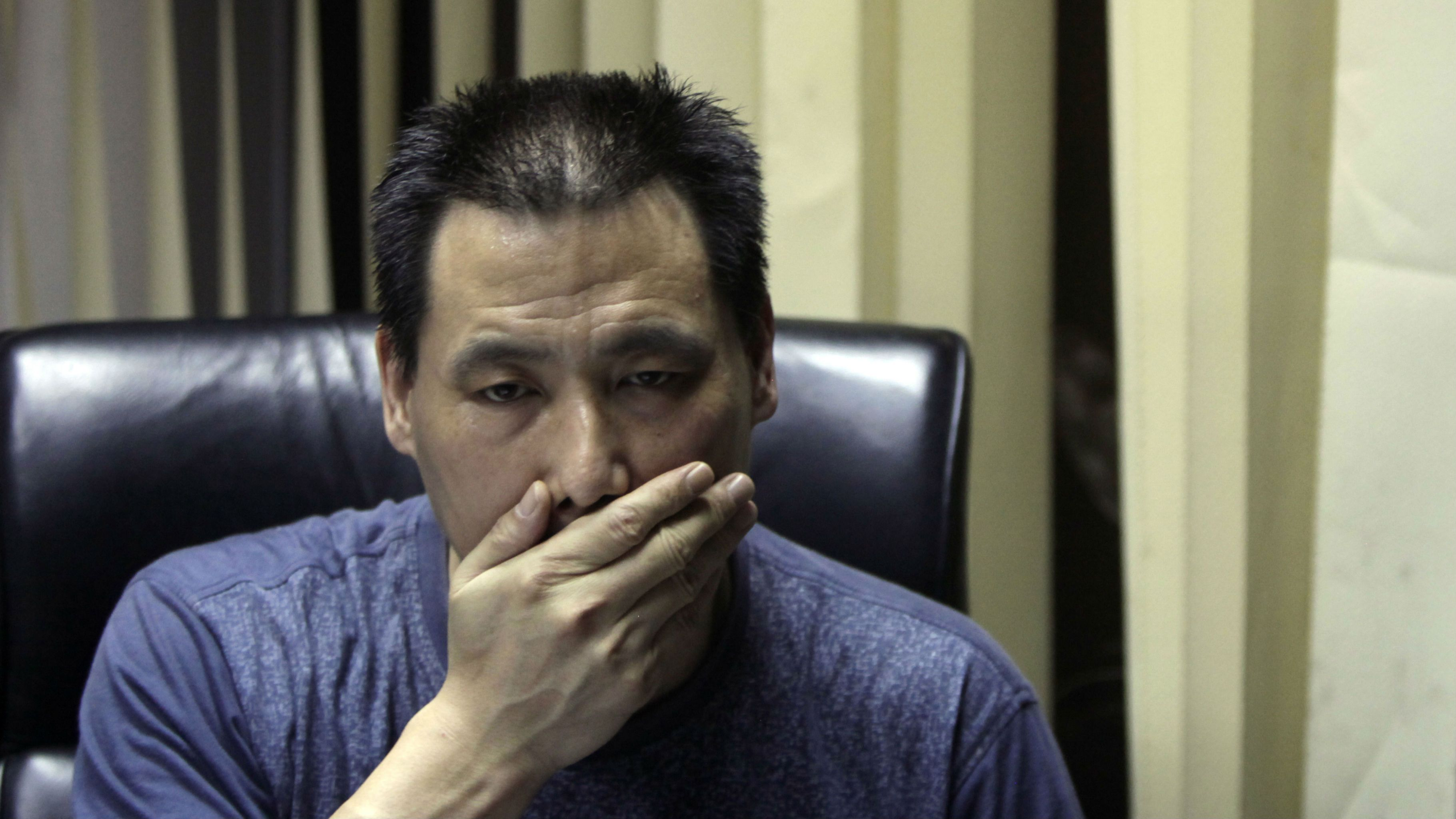 In this photo taken Wednesday, June 30, 2010, Chinese attorney Pu Zhiqiang wipes his mouth during an interview at his office in Beijing, China. Police on Friday, June 13, 2014 formally arrested the rights lawyer who is well known in China for his efforts to defend free speech, abolish labor camps and publicize abuses by police and Communist Party officials. (AP Photo/Ng Han Guan)