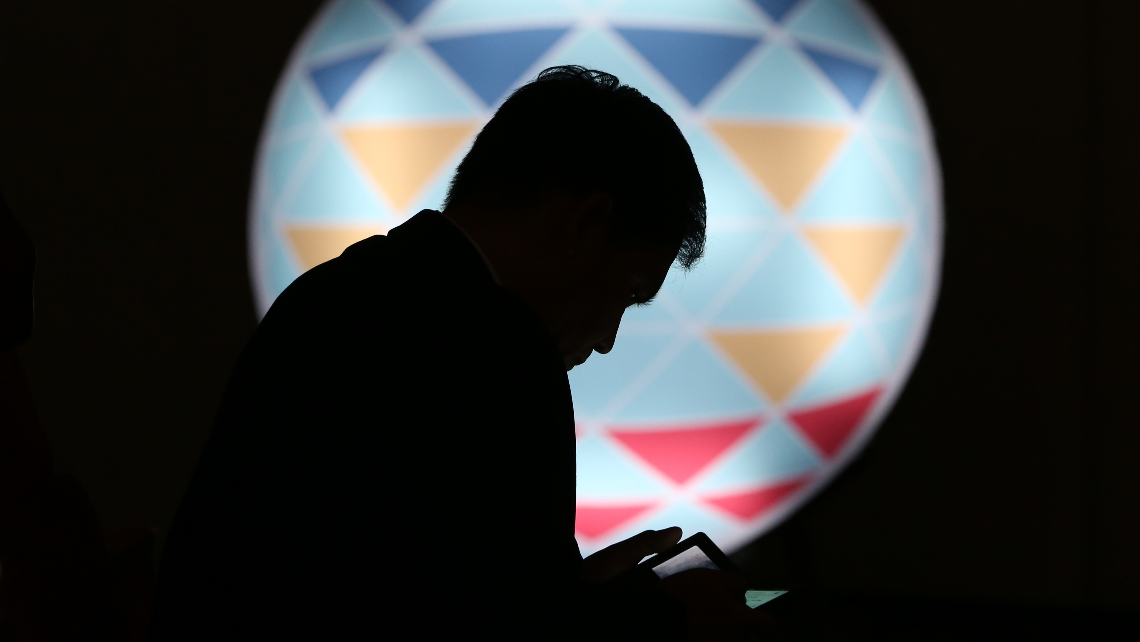 FILE - In this Sunday, Nov. 15, 2015, file photo, a Filipino checks his smartphone in front of the logo of APEC 2015 in Manila, Philippines. (AP Photo/Aaron Favila, File)