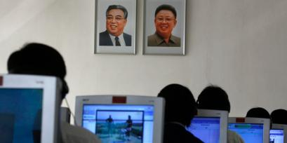 North Korean students use computers in a classroom with portraits of Kim Il Sung and Kim Jong Ill.