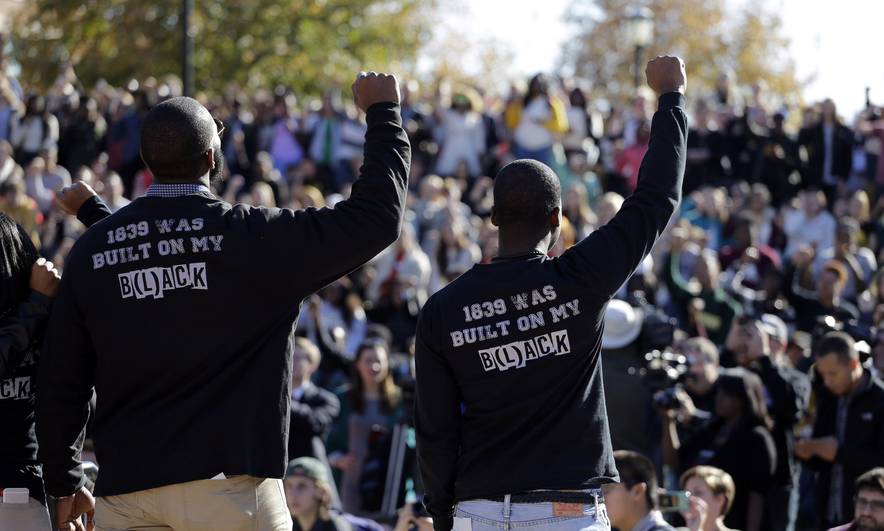 Members of the black student protest group, Concerned Student 1950, raise their arms while addressing a crowd following the announcement University of Missouri System President Tim Wolfe would resign Monday, Nov. 9, 2015, at the University of Missouri in Columbia, Mo. Wolfe resigned Monday with the football team and others on campus in open revolt over his handling of racial tensions at the school. (AP Photo/Jeff Roberson)