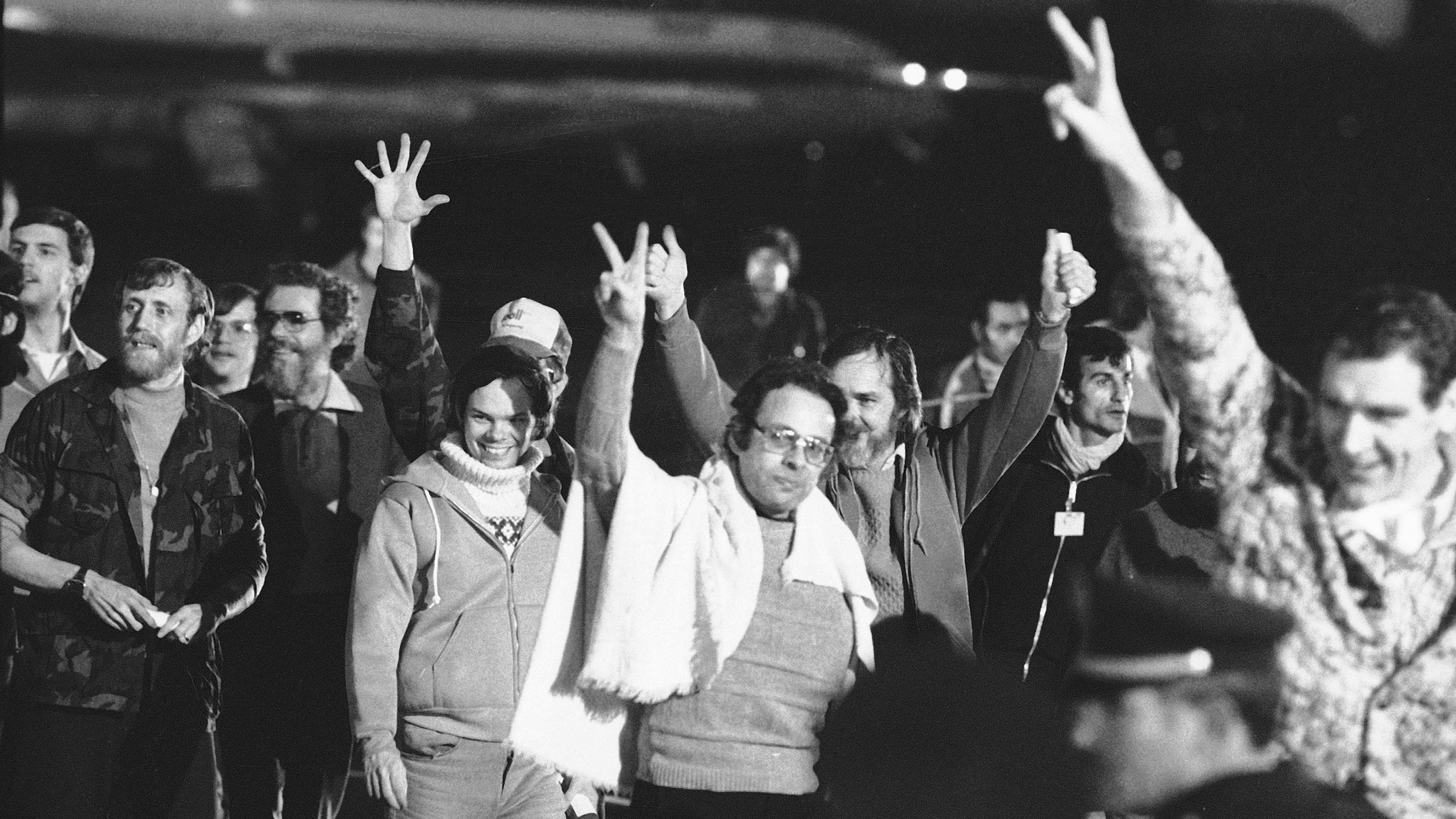 Iran hostages, A group of unidentified American hostages give the victory sign as they emerge from an Algerian aircraft in Algiers after their flight from Teheran where they had been held captive for 444 days in Iran, Jan. 21, 1981.