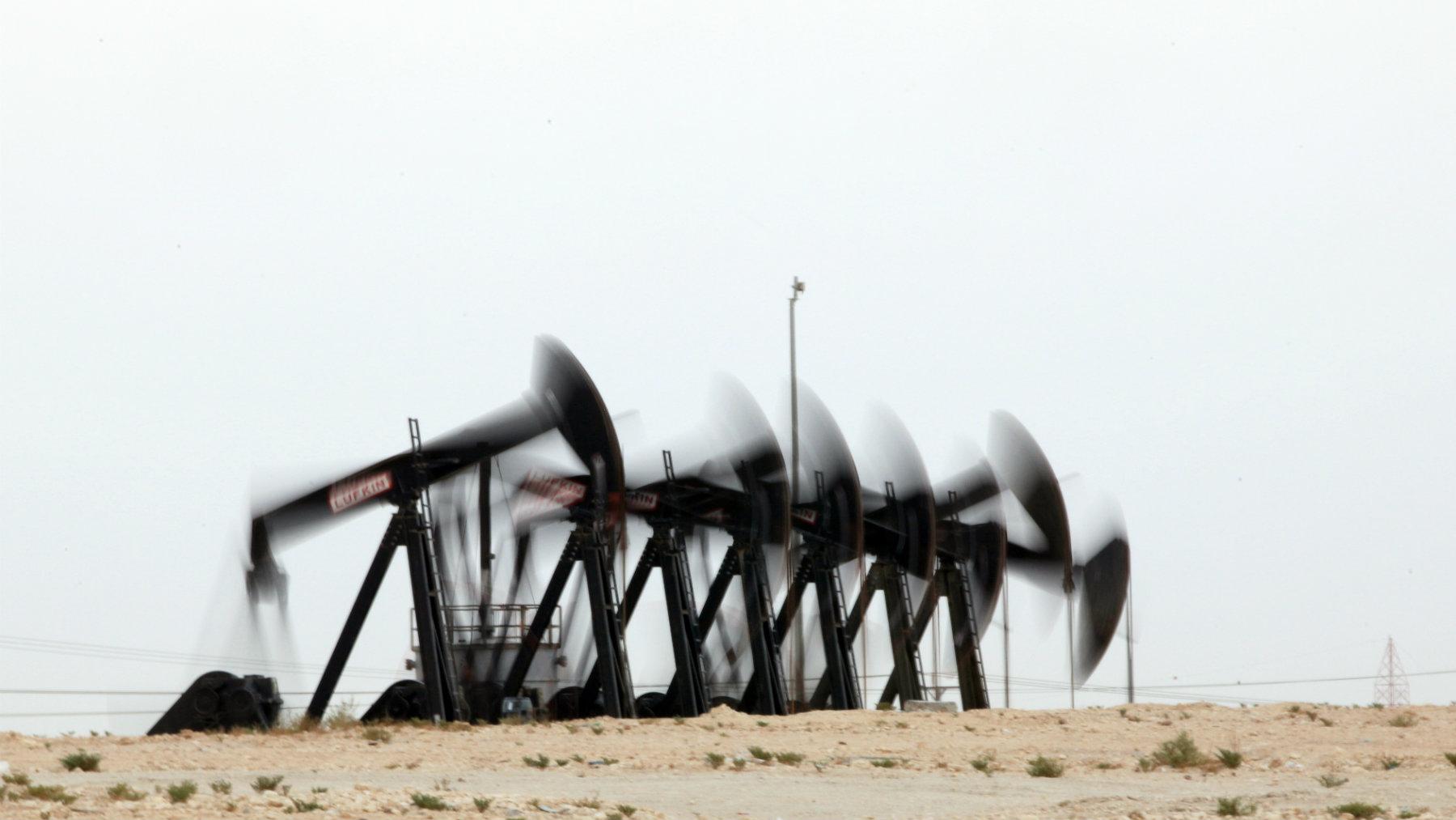 A row of oil pumps work in the desert oil fields of Sakhir, Bahrain.