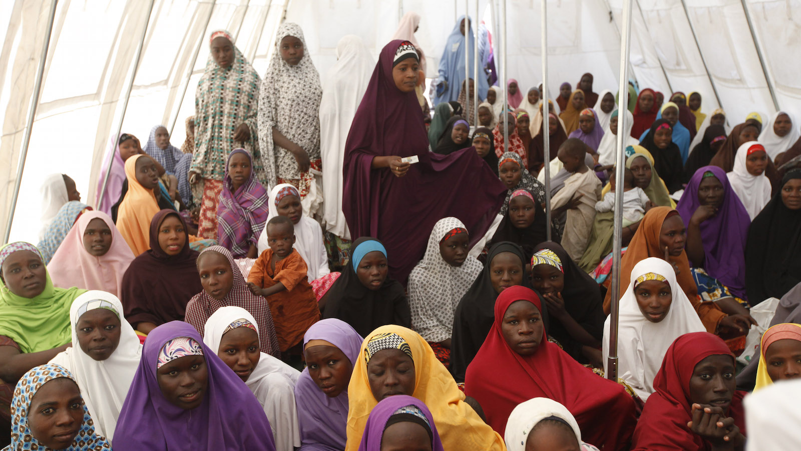 In this photo taken Monday, Dec. 7, 2015, children displaced by Boko Haram in an attack on their villages receive lectures in  a camp in Maiduguri, Nigeria. Attacks by Islamic extremist group Boko Haram in northeastern Nigeria and neighboring countries have forced more than 1 million children out of school, heightening the risk they will be abused, abducted or recruited by armed groups, the United Nations children's agency said Tuesday, Dec. 22, 2015. ()