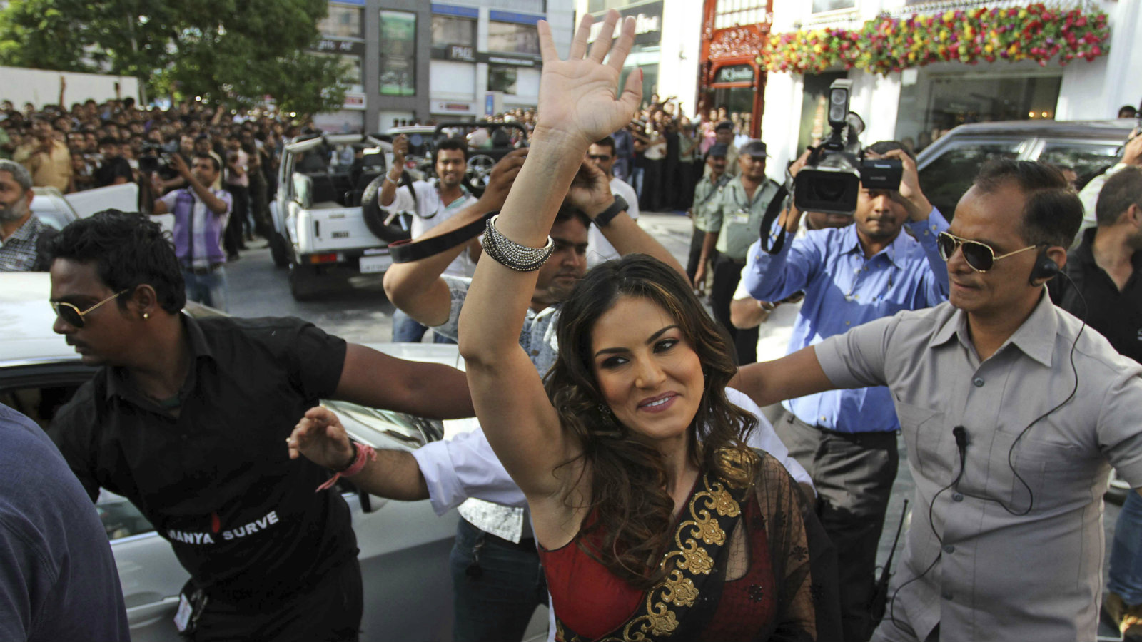 Film star Sunny Leone waves to fans after a press conference supporting her upcoming movie 'Shootout At Wadala' in Ahmadabad, India, Friday, April 26, 2013. The film based on growth of organized crime in late 70's and early 80's of Mumbai, will be released on May 3, according to a press release.