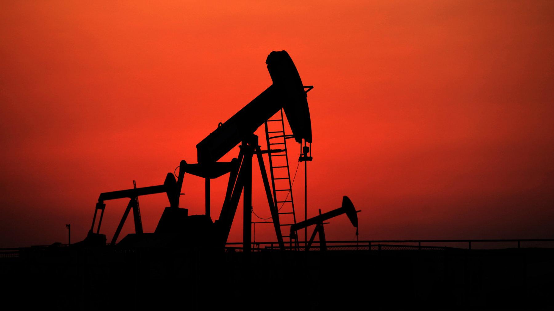 Oil pumps work at sunset in the desert oil fields of Sakhir, Bahrain