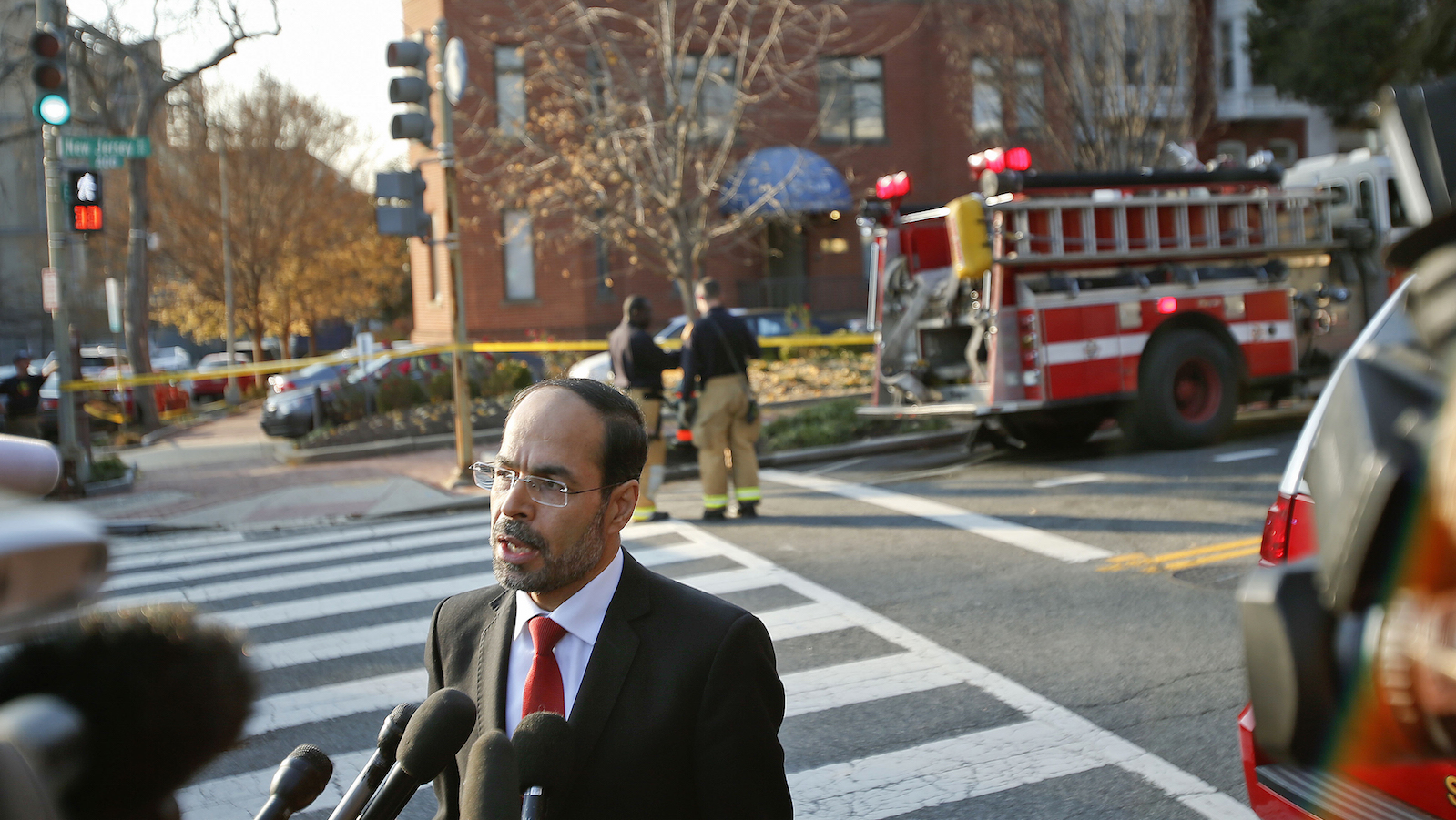 Council on American-Islamic Relations (CAIR) Executive Director and co-founder Nihad Awad speaks to members of the media as firefighters are seen in the background at CAIR headquarters on Capitol Hill in Washington, Thursday, Dec. 10, 2015, after the building was evacuated. A spokesman for a Muslim group said its headquarters on Capitol Hill have been evacuated after staffers came in contact with a suspicious substance that arrived in the mail.