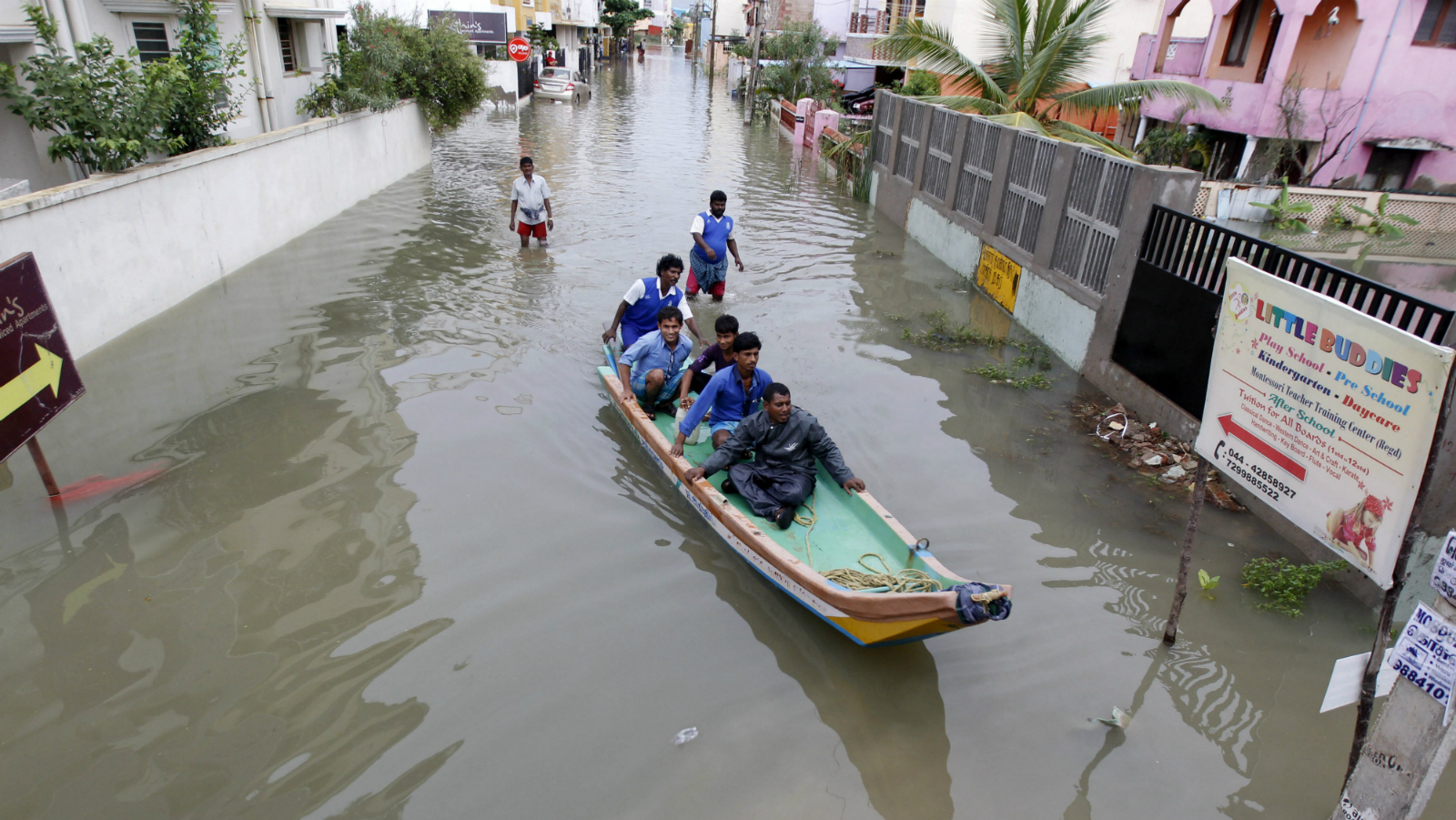 Rescue workers on a boat move people to safety at a residential area that was water-logged following heavy rains in Chennai, Tamil Nadu state, India, Monday, Nov.16, 2015. Incessant rains that lashed the city since Saturday night flooded several parts of Chennai. (AP Photo/Arun Sankar K)