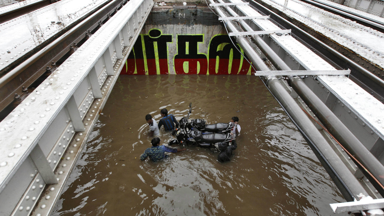 Indian commuters carry their motorbikes on a submerged cart as they wade through a waterlogged subway in Chennai, India, Monday, Nov. 9, 2015. Heavy rains continue to lash several parts of the city after the India Meteorological Department alerted a cyclone warning on the Bay of Bengal coast likely to make landfall between Chennai and Puducherry on Monday evening, according to local reports.