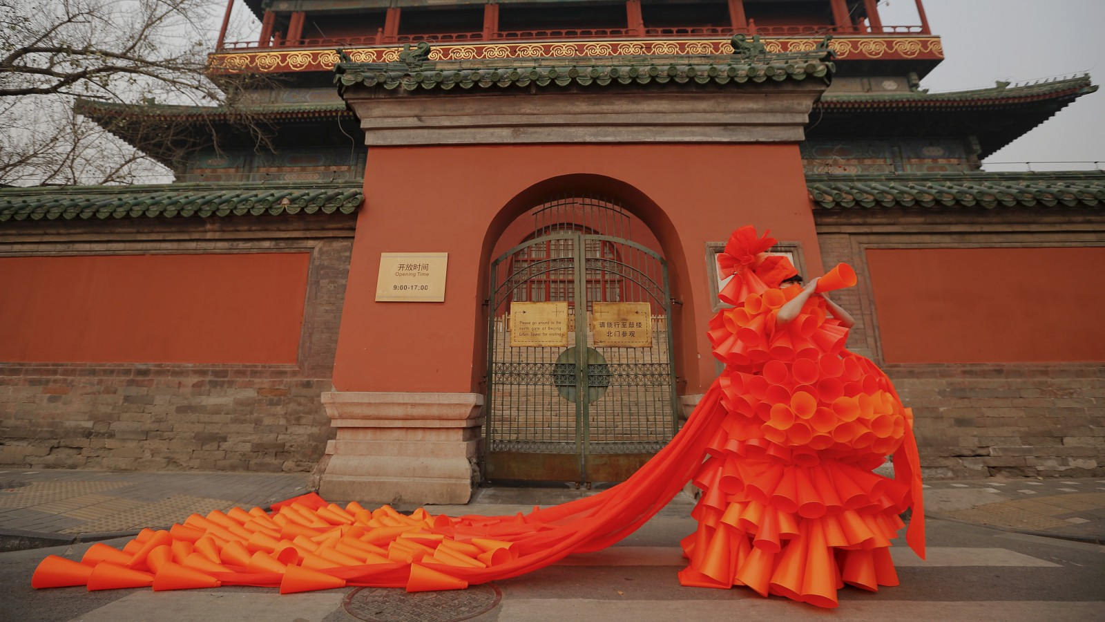 "Chinese artist Kong Ning symbolically makes warning sounds in her costume made of hundreds of orange plastic blowing horns during her art performance raising awareness of the hazardous smog in front of the Drum tower in a historical part of Beijing on a very polluted day December 7, 2015. Kong, whose works include themes related to China's air pollution problem, named her new performance ""The Orange Horns Bride Marries the Blue Sky"" and presented it dressed in orange, the colour of the second highest pollution alert level issued again in Beijing as hazardous smog blankets the capital.   REUTERS/Damir Sagolj - RTX1XIMS"
