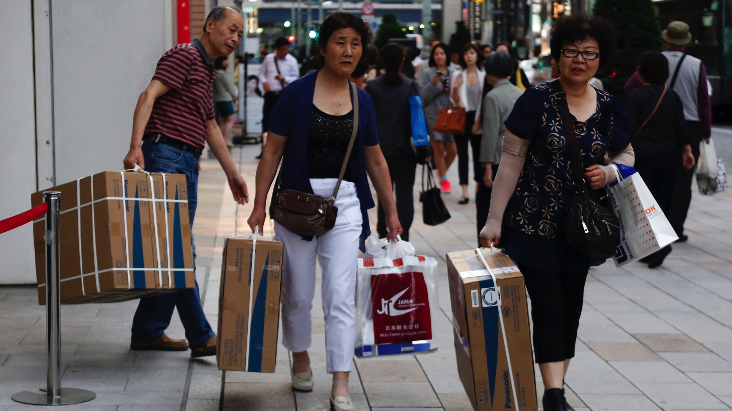 Chinese tourists carry packages of Panasonic Corp's washlet along the Ginza Shopping district