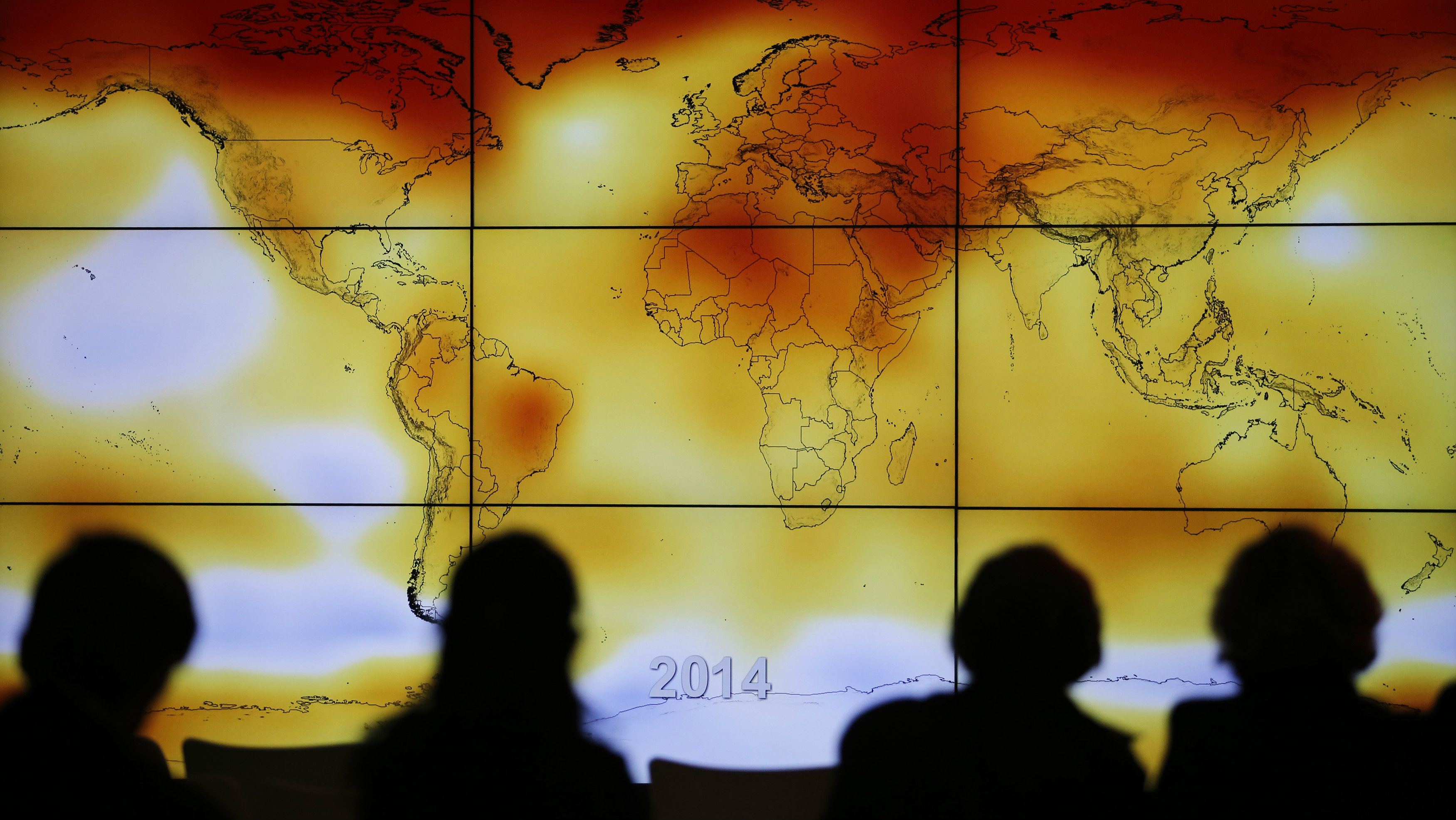 Participants are seen in silhouette as they look at a screen showing a world map with climate anomalies during the World Climate Change Conference 2015 (COP21) at Le Bourget, near Paris, France, December 8, 2015. REUTERS/Stephane Mahe TPX IMAGES OF THE DAY