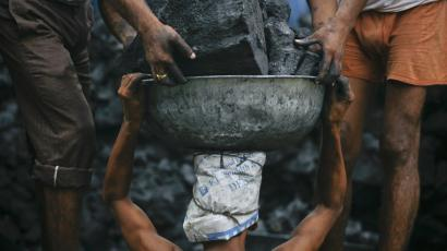 Labourers unload coal from a supply truck at a wholesale market in Noida, in the outskirts of New Delhi.