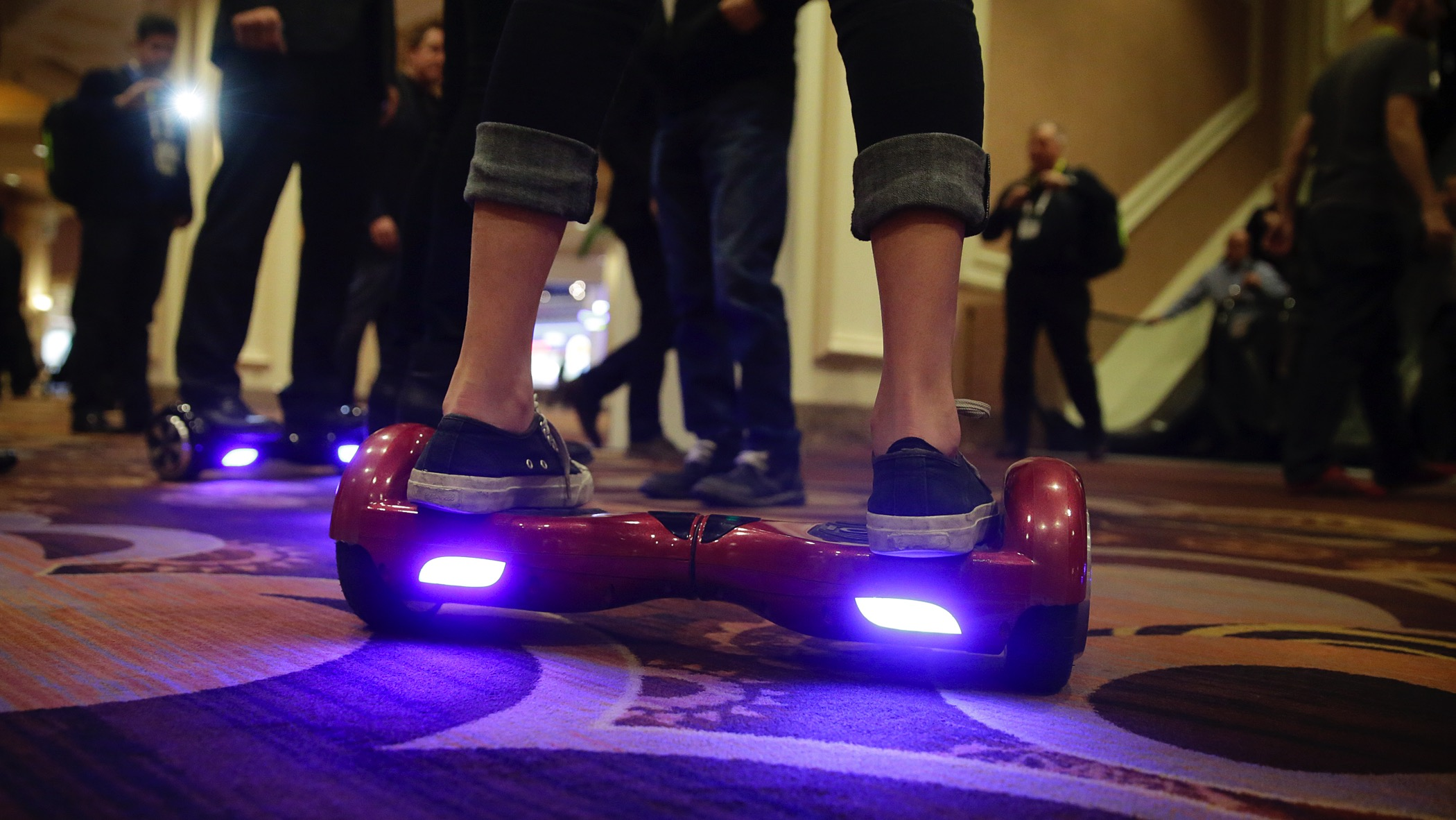 A woman rides an IO Hawk, a self-balancing motorized personal transporter at the International CES, Monday, Jan. 5, 2015, in Las Vegas. The world's largest annual trade show officially opens Tuesday. (AP Photo/Jae C. Hong)