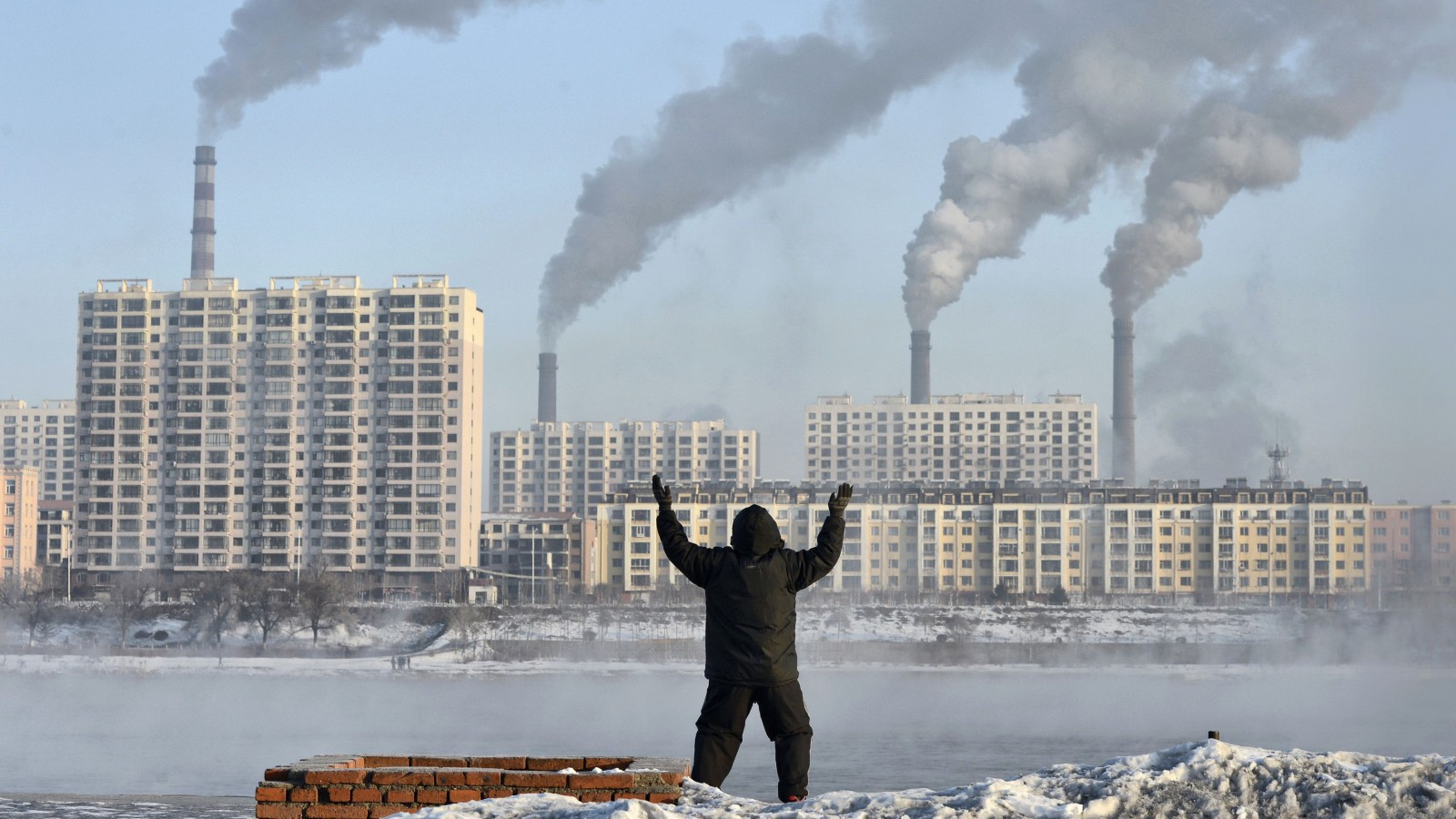 An elderly man exercises in the morning as he faces chimneys, China.