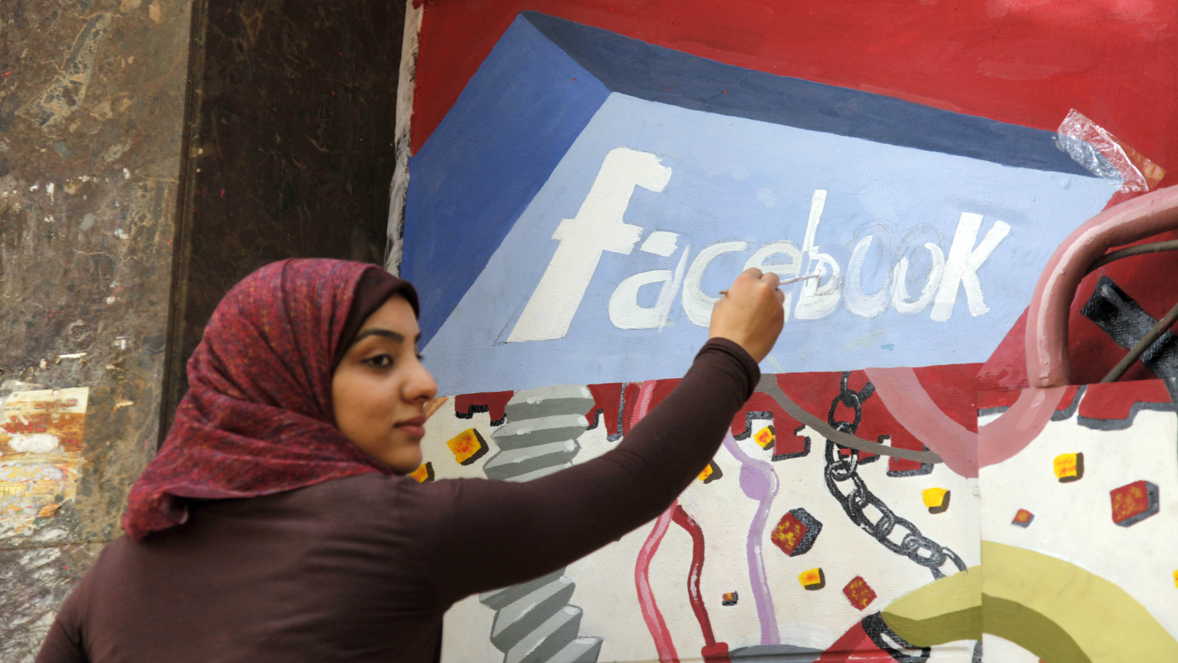An art student from the University of Helwan paints the Facebook logo on a mural commemorating the revolution that overthrew Hosni Mubarak in the Zamalek neighborhood of Cairo, Egypt, Wednesday, March 30, 2011. They painted icons of the protests that began Jan. 25, including Facebook, which activists used to organize protests, and symbols of Muslim-Christian unity.