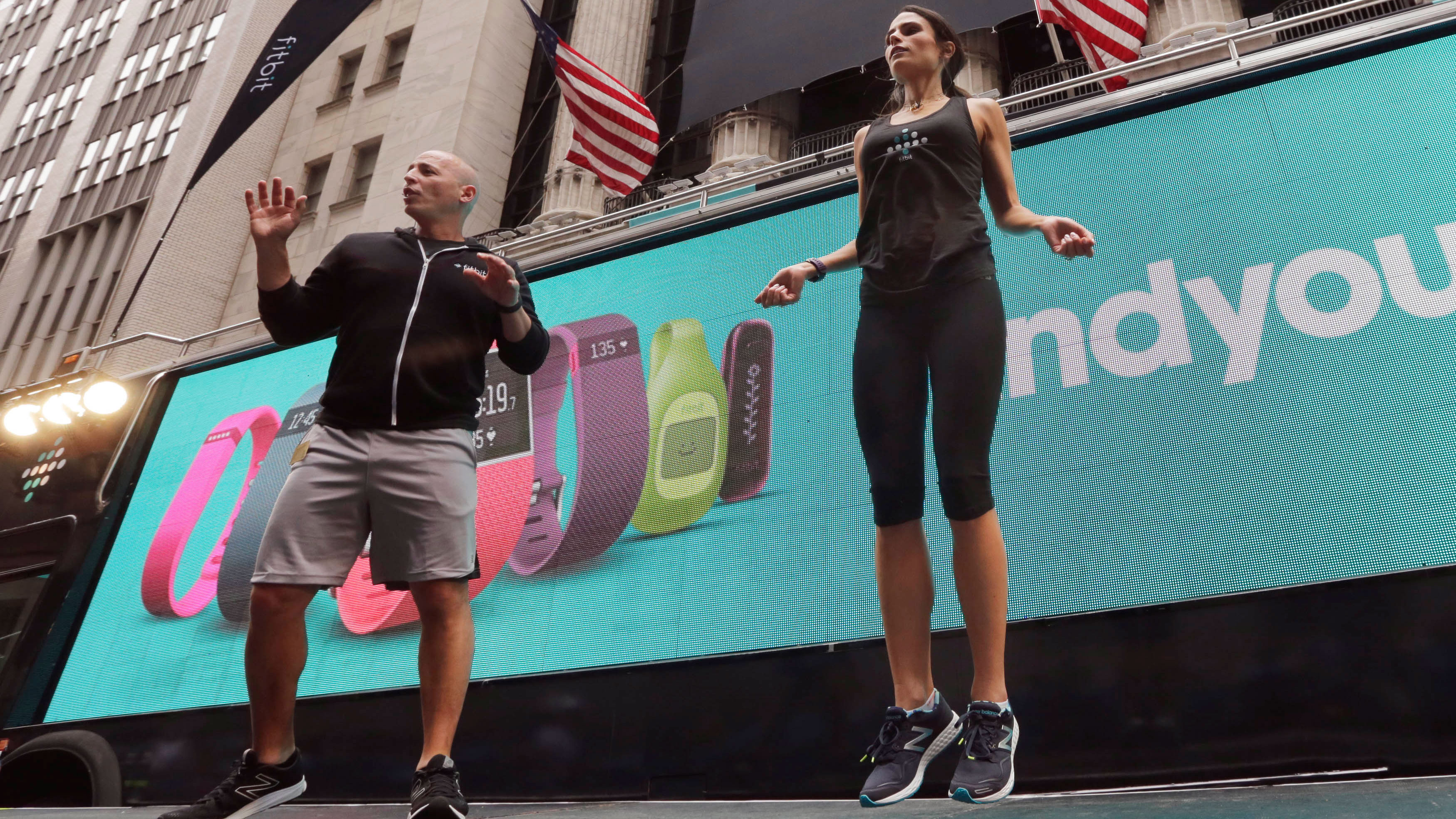 Fitness expert Harley Pasternak, left, and actress Jordana Brewster lead a work out, on behalf of Fitbit, in front of the New York Stock Exchange, Thursday, June 18, 2015. Fitbit flexed some muscle Thursday and its shares rocketed 50 percent higher in the first day of trading for the fitness tracking gear maker. (AP Photo/Richard Drew)