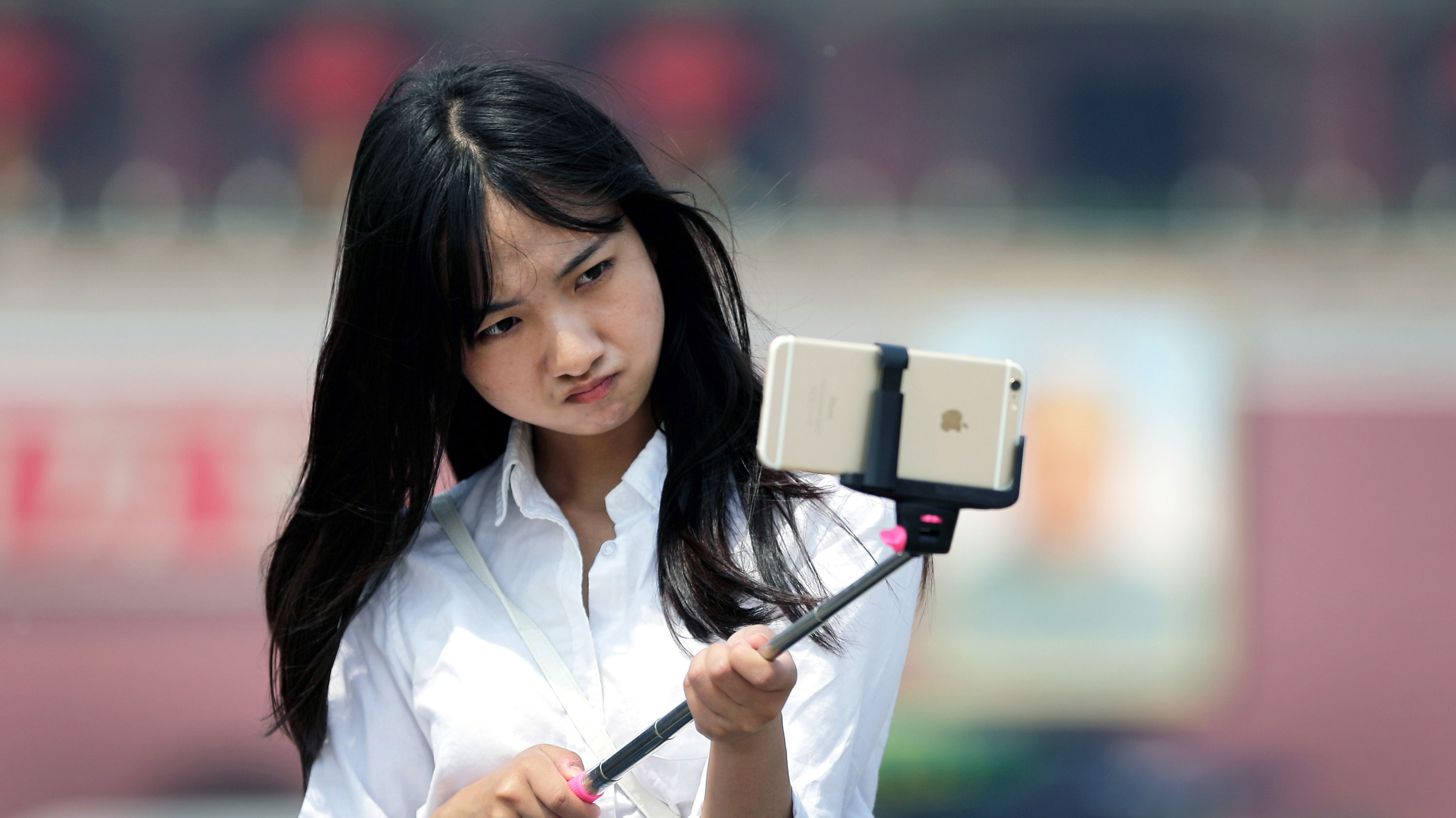 A woman reacts as she uses a selfie stick to take a photo of herself at Tiananmen Square in Beijing, China, Thursday, April 30, 2015. Selfie sticks are gaining popular in China, and many people are using them at popular tourist destinations. (AP Photo/Andy Wong)