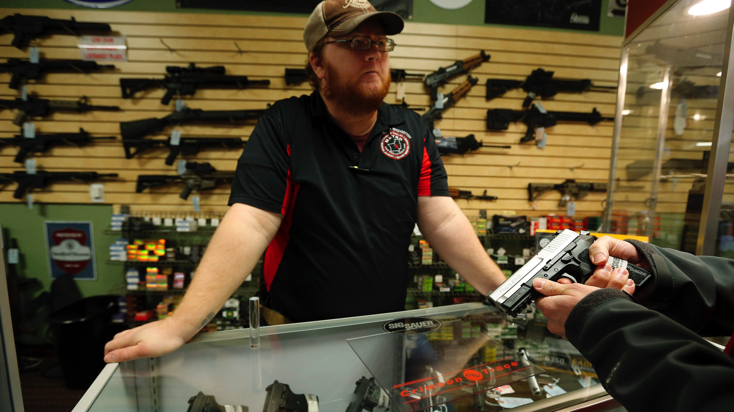 Metro Shooting Supplies' employee Chris Cox speaks to a customer about the purchase of a 9mm handgun in Bridgeton