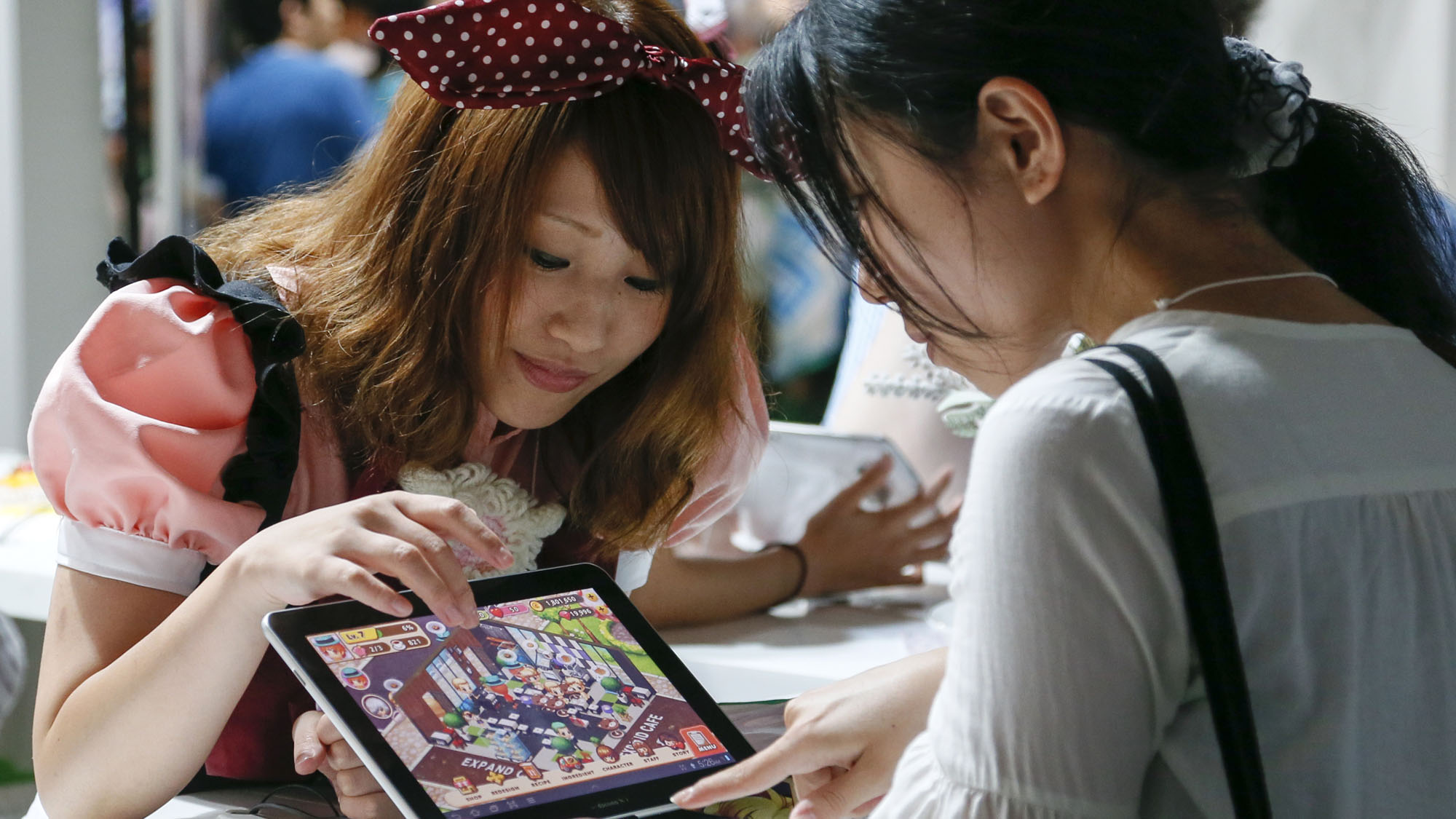 A visitor tries to play a game on a tablet at the booth of WeMade Entertainment, a South Korean company developing and running online games, during the Tokyo Game Show 2012 at Makuhari Messe in Chiba, east of Tokyo, Japan, 21 September 2012. The game show takes place from 20 to 23 September.