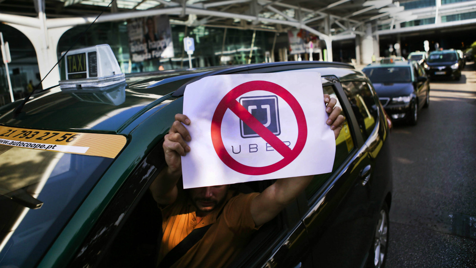 A taxi driver hold a crossed out Uber sign during a protest action in Lisbon, Portugal, 08 September 2015. More than a thousand taxi drivers protested in Lisbon against ride-sharing company Uber, blocking roads and stalling traffic during morning rush hour as tensions rise in the city over the mobile app ride service.