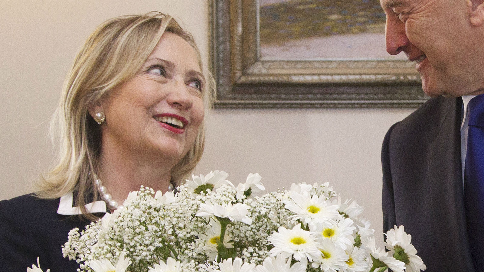 Hillary Clinton receiving a bouquet of flowers from the President of Latvia.