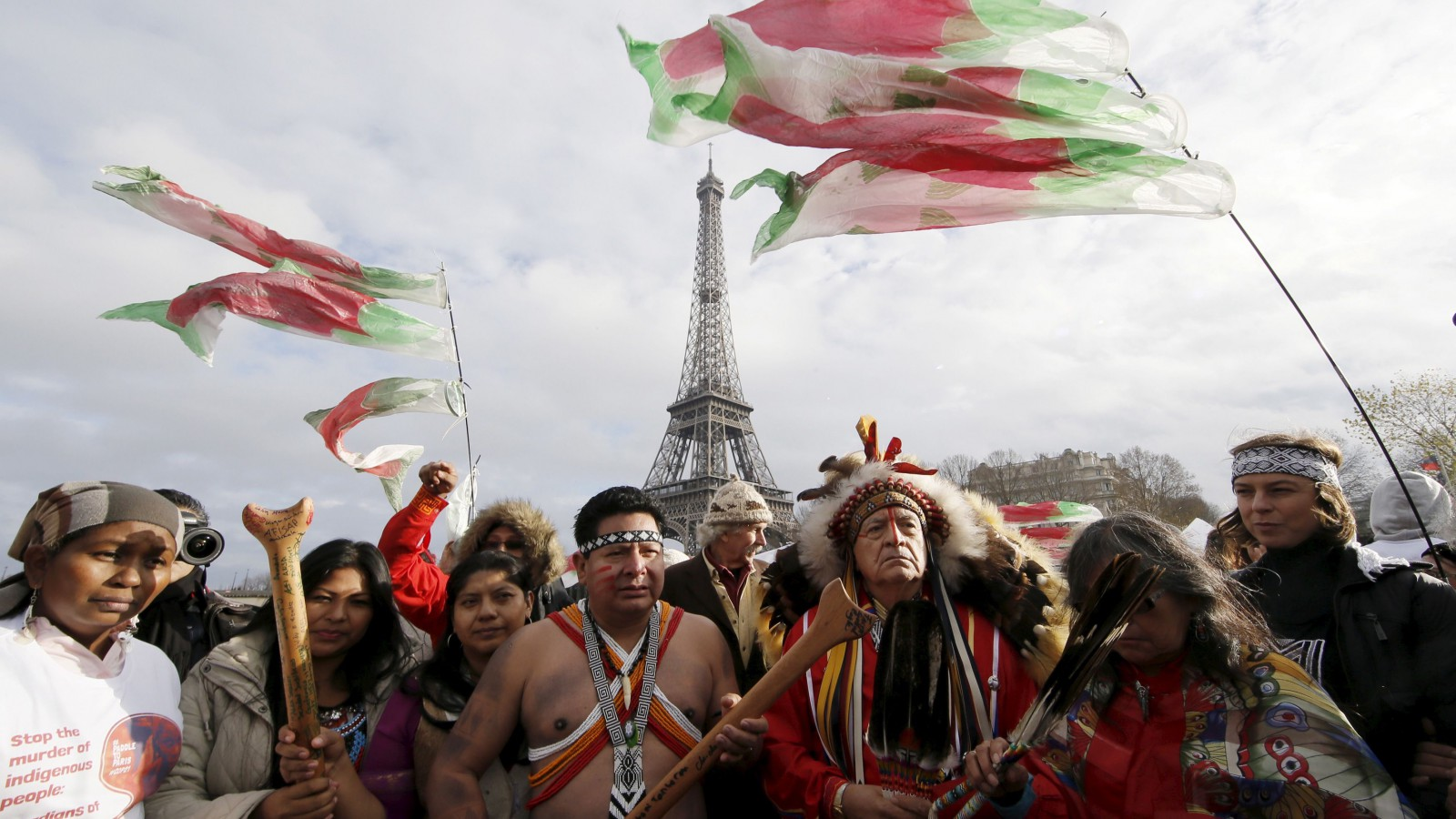 Indigenous leaders from all over the world pray as they sail on the Seine.