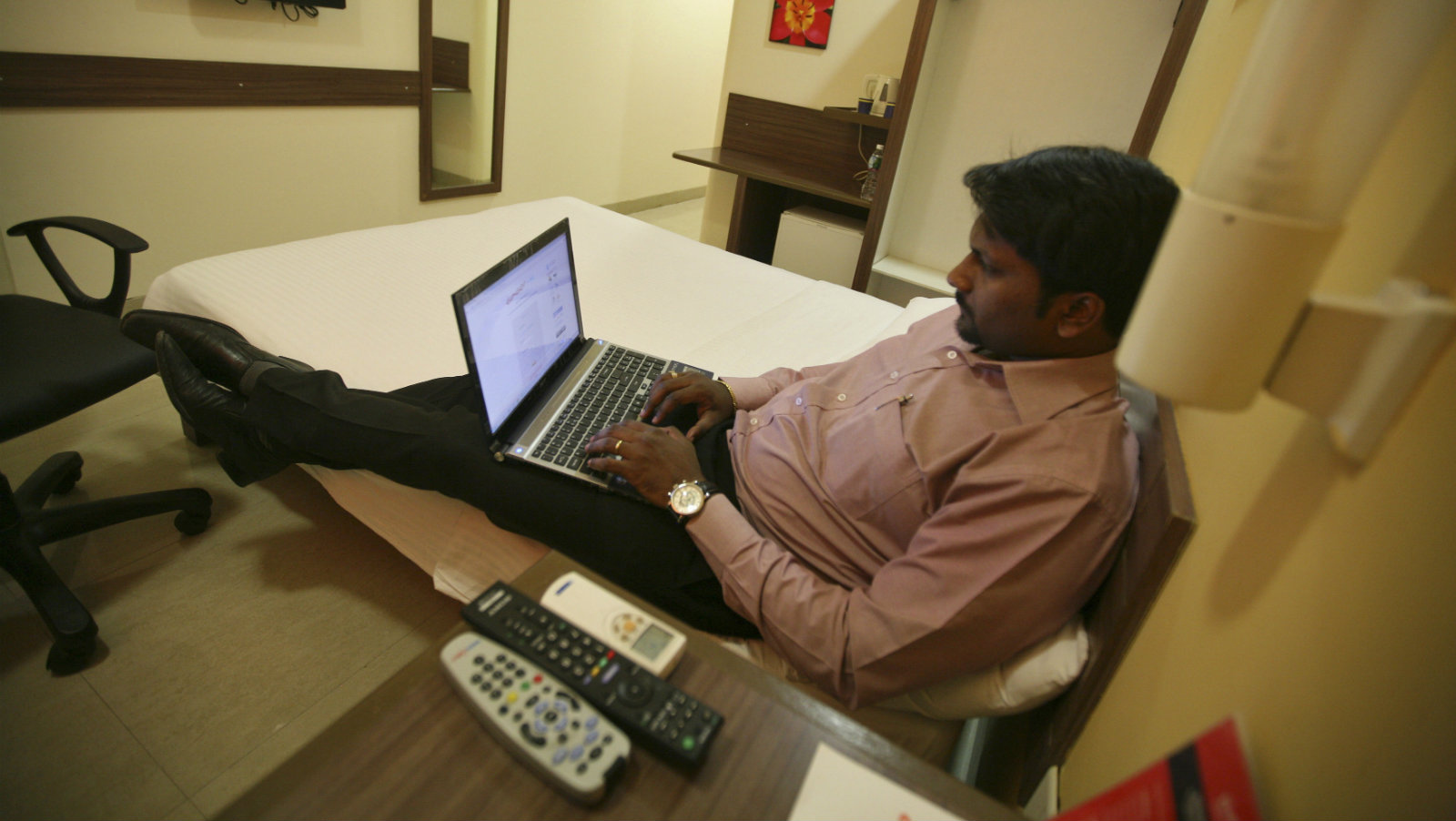A guest works on a laptop inside his room at the Tata Group's Indian Hotels Co. Ginger chain in the western Indian city of Ahmedabad May 5, 2012. Rising spending by domestic travellers in India and Indonesia is prompting international hoteliers to build budget and mid-scale brands in the world's second and fourth largest populations. Ginger, run by the Tata Group's Indian Hotels Company, owner of Taj hotels, has 24 budget hotels in India with plans to grow to 75 hotels over the next four years. Picture taken May 5, 2012.