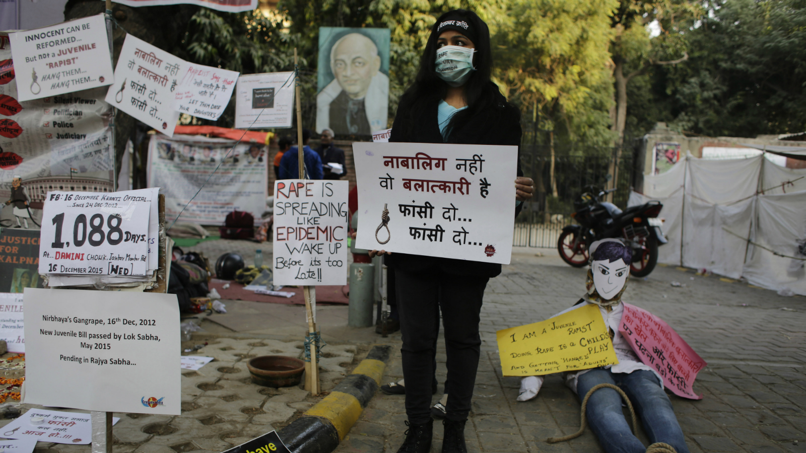 "An Indian woman holds a placard which reads, ""He is not a juvenile but a rapist, hang him"" during a demonstration to commemorate the third anniversary of December 16, 2012 rape in a moving bus in New Delhi, India, Wednesday, Dec. 16, 2015. The protestors were reacting to the reports that one of the convicts in the case will be freed from the prison since he is a juvenile. (AP Photo/Altaf Qadri)"