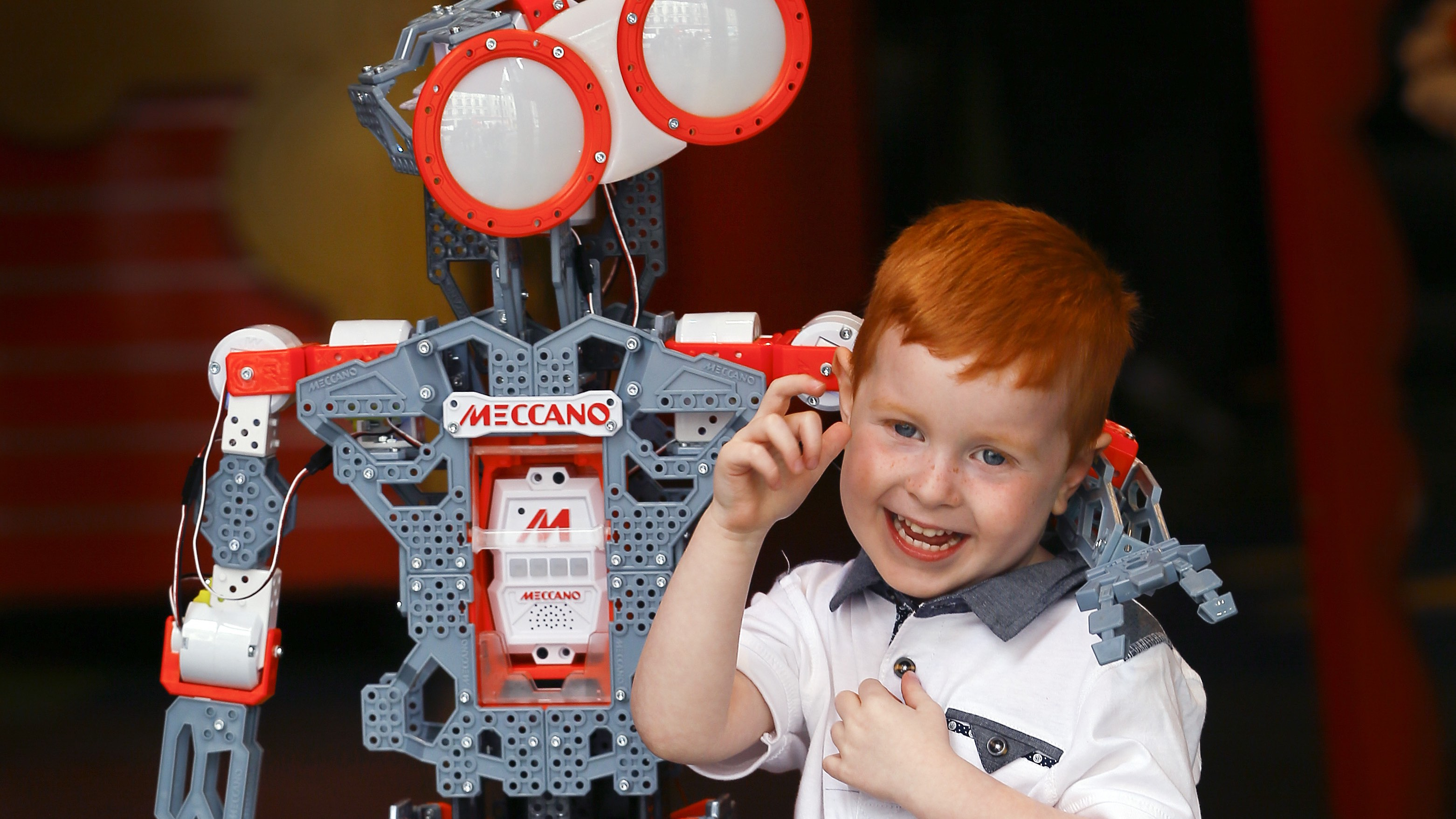 Tristan Robertson Jeyes, 4, gets a hug from a Meccanoid G15 KS robot, pre-programmed with over 1000 phrases, in London, Thursday, June 25, 2015. Christmas came early on Thursday as children were invited to play with toys that Hamleys toy shop have predicted to be best sellers this Christmas. (AP Photo/Kirsty Wigglesworth)