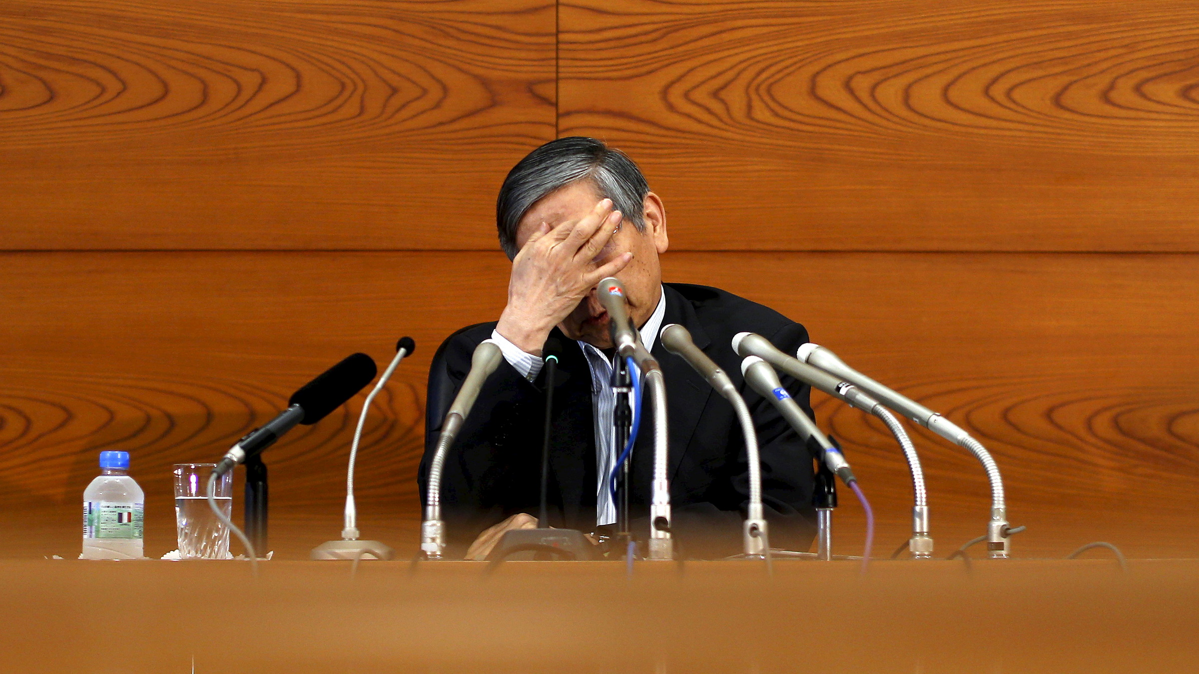 Bank of Japan (BOJ) Governor Haruhiko Kuroda touches his face during a news conference at the BOJ headquarters in Tokyo, July 15, 2015. The Bank of Japan trimmed its economic growth forecast on Wednesday but held off on offering fresh stimulus, convinced that an expected pick up in consumption will help accelerate inflation toward its 2 percent target.