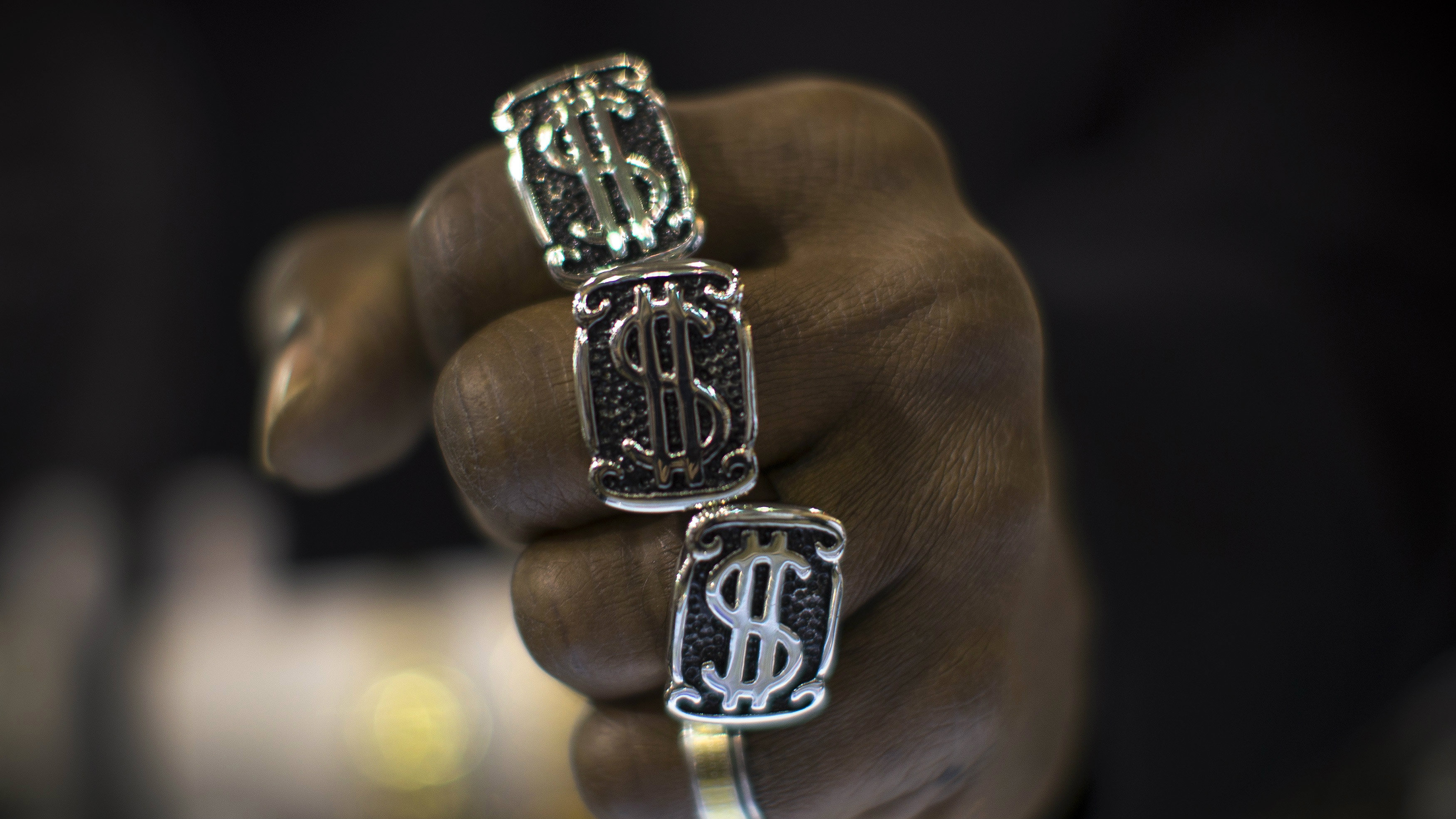 man's fist with dollar signs