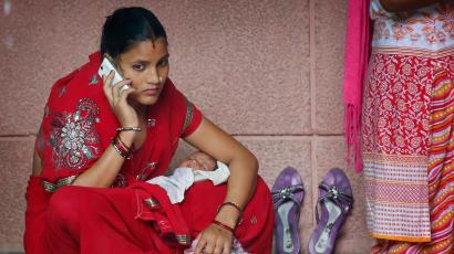 An Indian mother speaks on the mobile phone as she sits with her infant child on her lap at a government hospital in Allahabad, India, Thursday, Aug. 27, 2015. Indian Prime Minister Narendra Modi on Thursday inaugurated a two-day summit of 24 countries on maternal and child mortality in New Delhi. (AP Photo/Rajesh Kumar Singh)