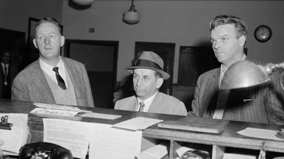 Meyer Lansky, 55-year-old figure in Havana gambling operations, is flanked by detectives as he is booked on a vagrancy charge in New York, Feb. 12, 1958. He was questioned in connection with last year's slaying of gangster Albert Anastasia.