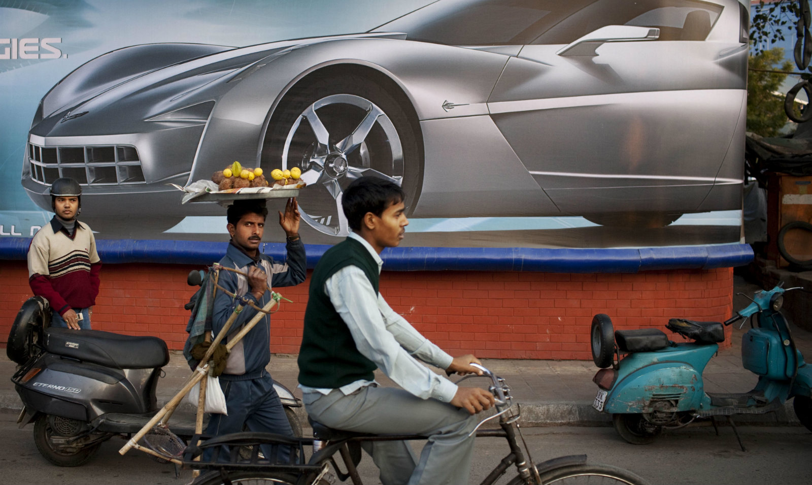 Indians pass a billboard advertisement for an American sports car in New Delhi, India, Wednesday, Jan. 25, 2012. Sales of automobiles in the world's largest democracy have steadily increased increased in recent years with the growth of the burgeoning middle class.